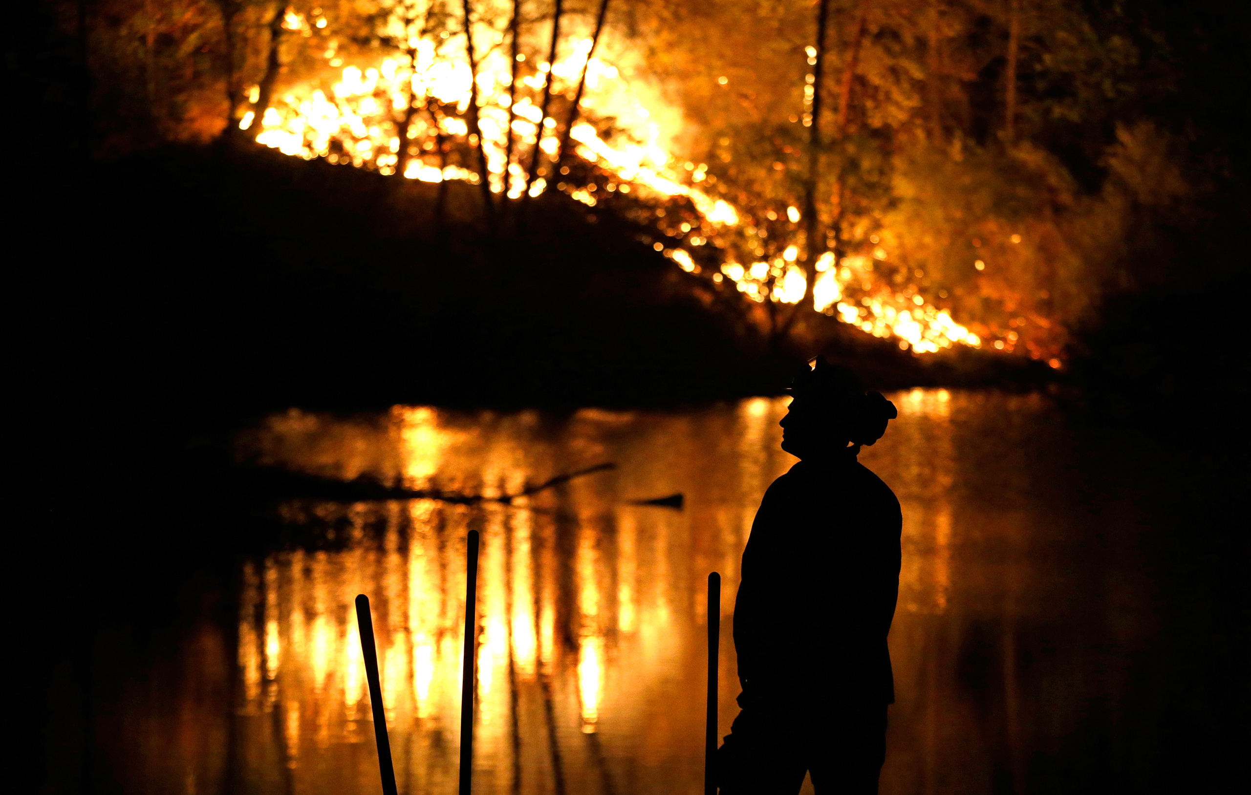 A firefighter stands near a wildfire in Middletown, Calif., on Sept. 13, 2015.