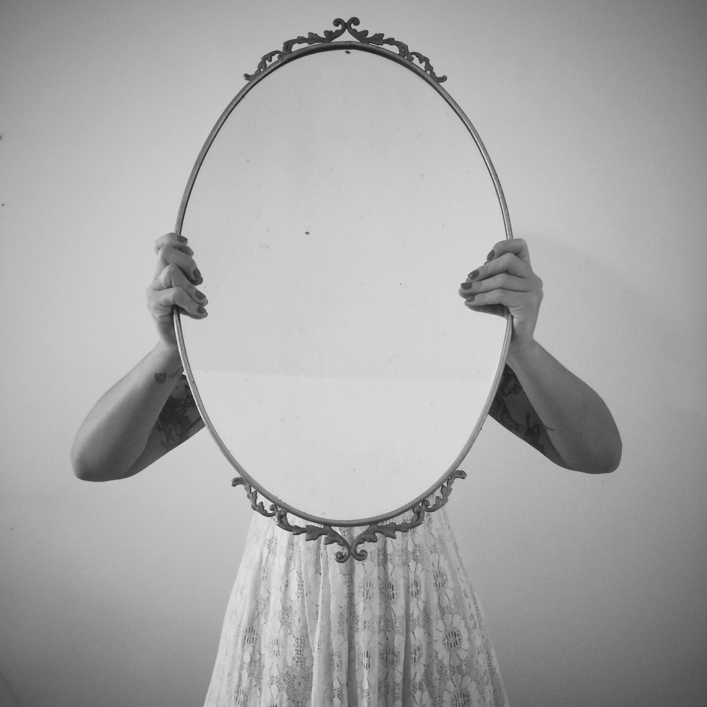 Woman Holding Mirror Against Wall
