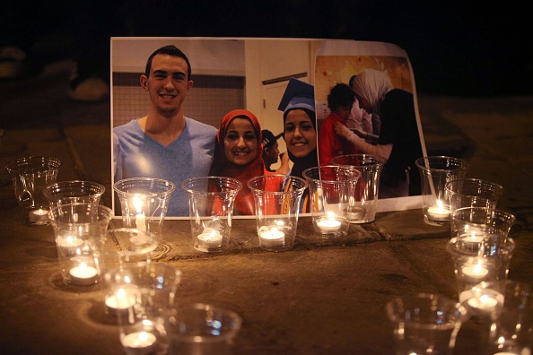 Candles are seen as a group of demonstrators gather in front of  American Embassy in Amman to protest against the Chapel Hill shooting, in Amman, Jordan on Feb. 16, 2015.