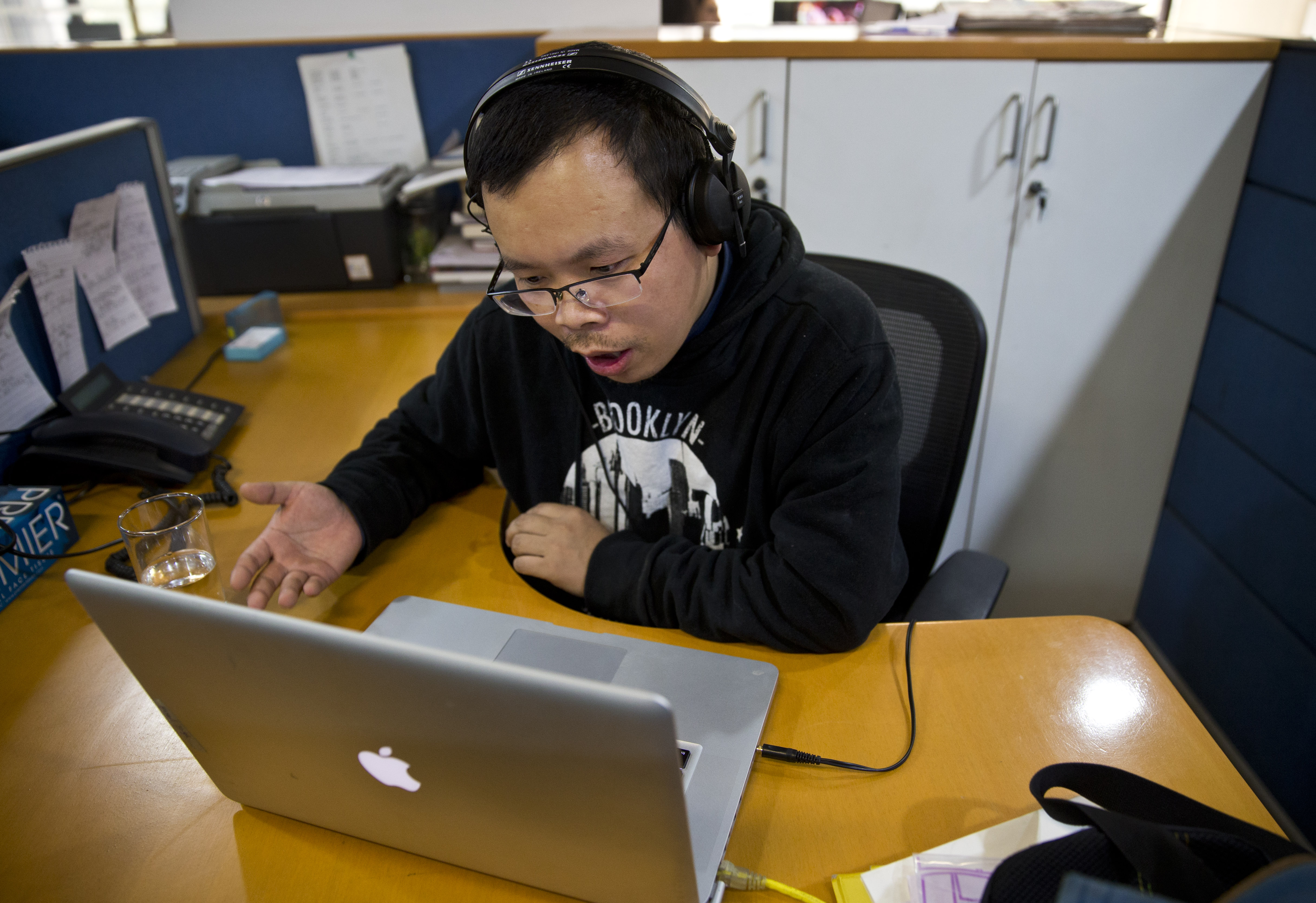 In this Nov. 20, 2015, file photo, Chinese journalist Li Xin talks to an Associated Press reporter over Skype, at the Associated Press office in New Delhi, India