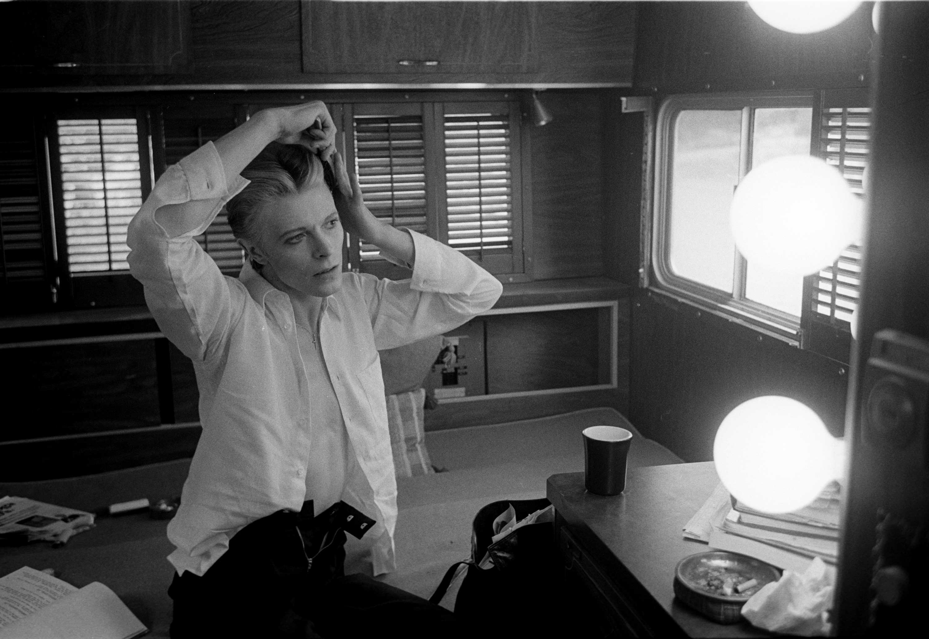 Steve Schapiro: Bowie in his dressing room  trailer, combing his hair, on the set of The Man Who Fell to Earth, New Mexico, 1975.