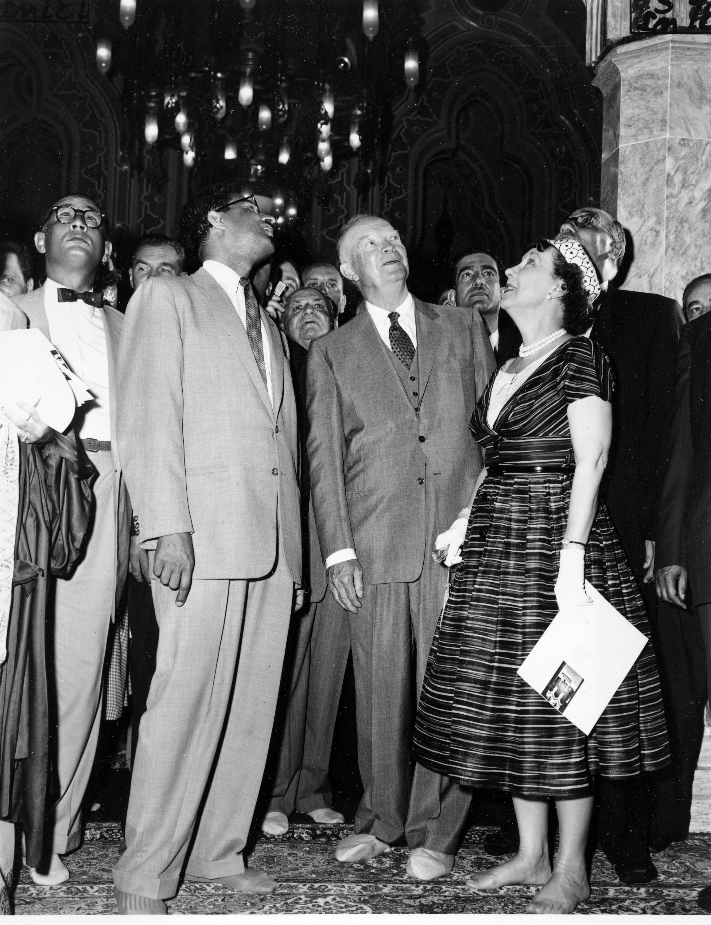 First lady Mamie Doud Eisenhower and U.S. President Dwight D. Eisenhower stand shoeless as they admire the architectural details pointed out by Sheikh Abdullah Al-Khayyal, Saudi Arabian ambassador, at the dedication ceremony of the Islamic Center and Mosque, in Washington, on June 28, 1957.