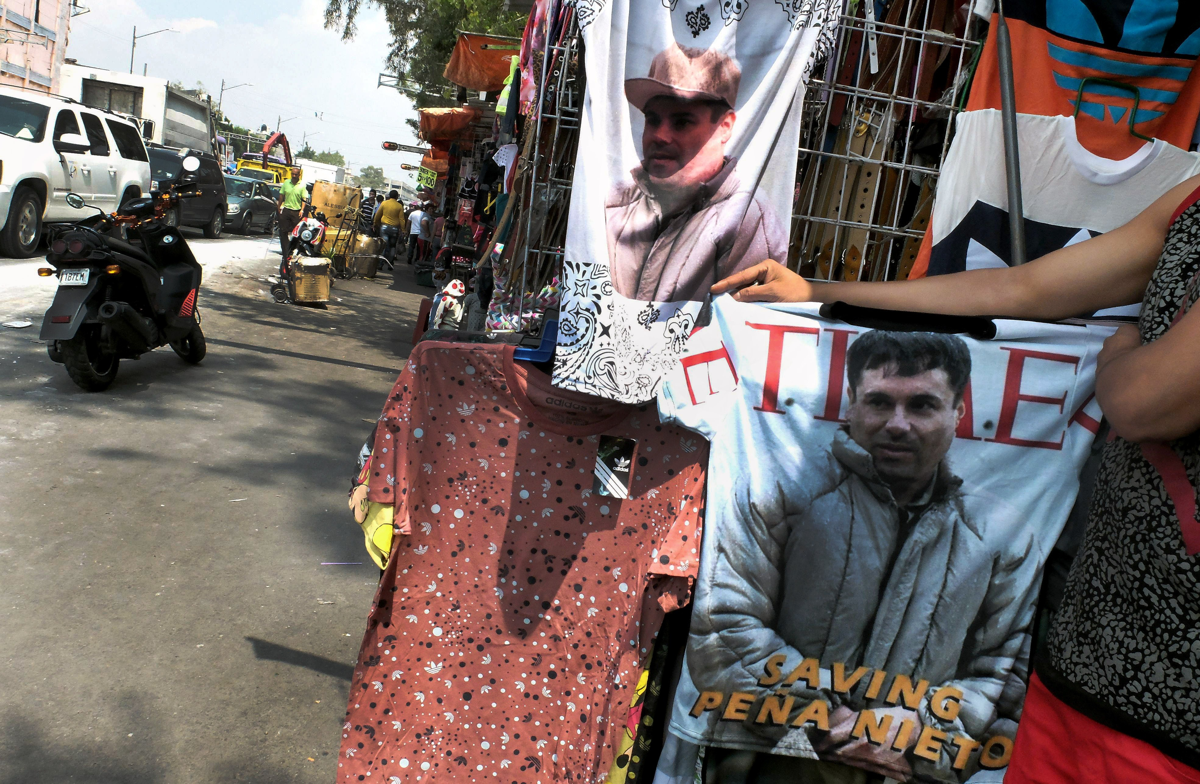 A vendor shows a t-shirt with the face of Joaquin  El Chapo  Guzman for sale  in Mexico City on July 20, 2015.