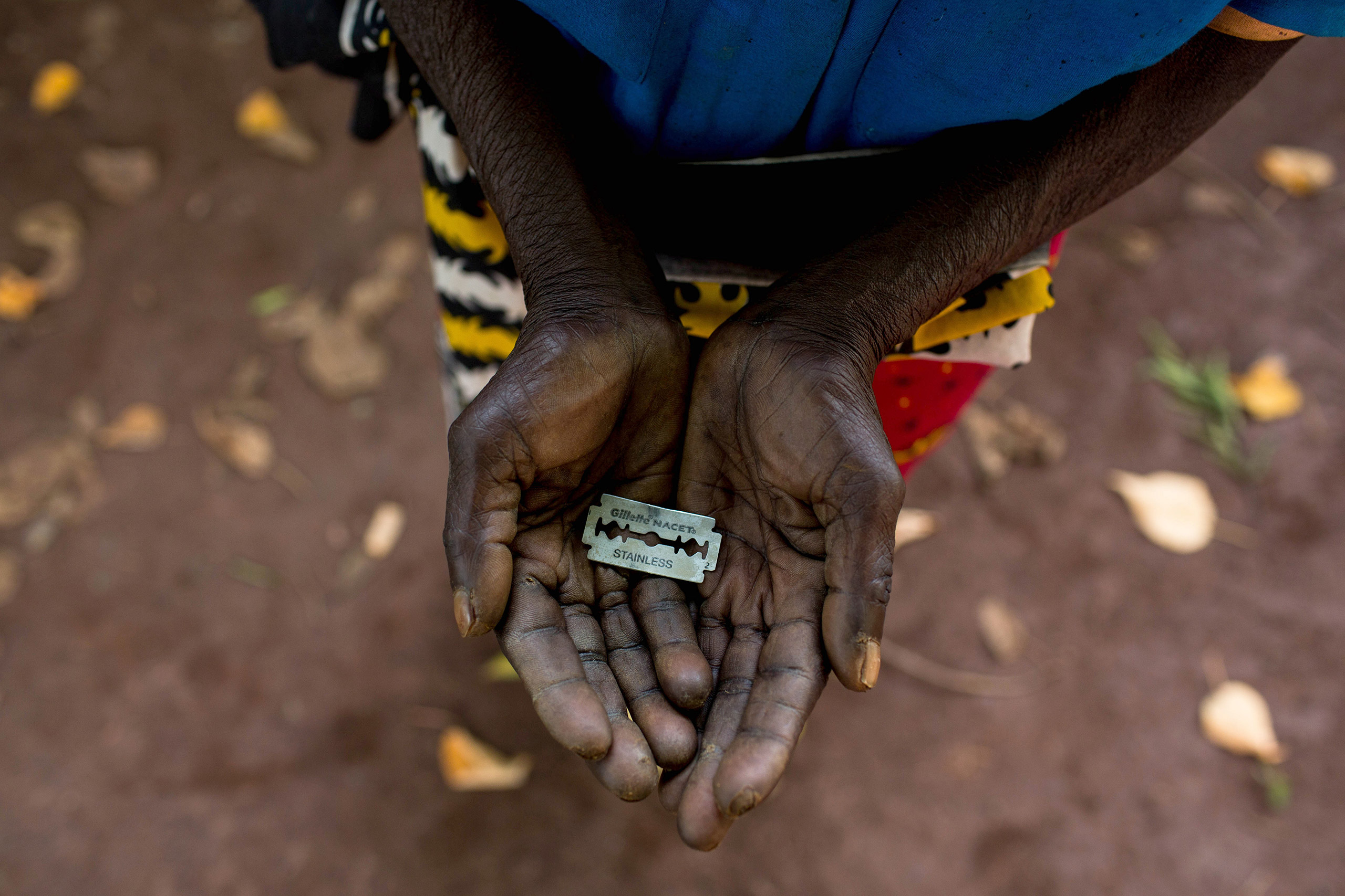 A woman shows the razor blade that she uses to cut girls' genitals in Mombasa, Kenya, June 25, 2015.