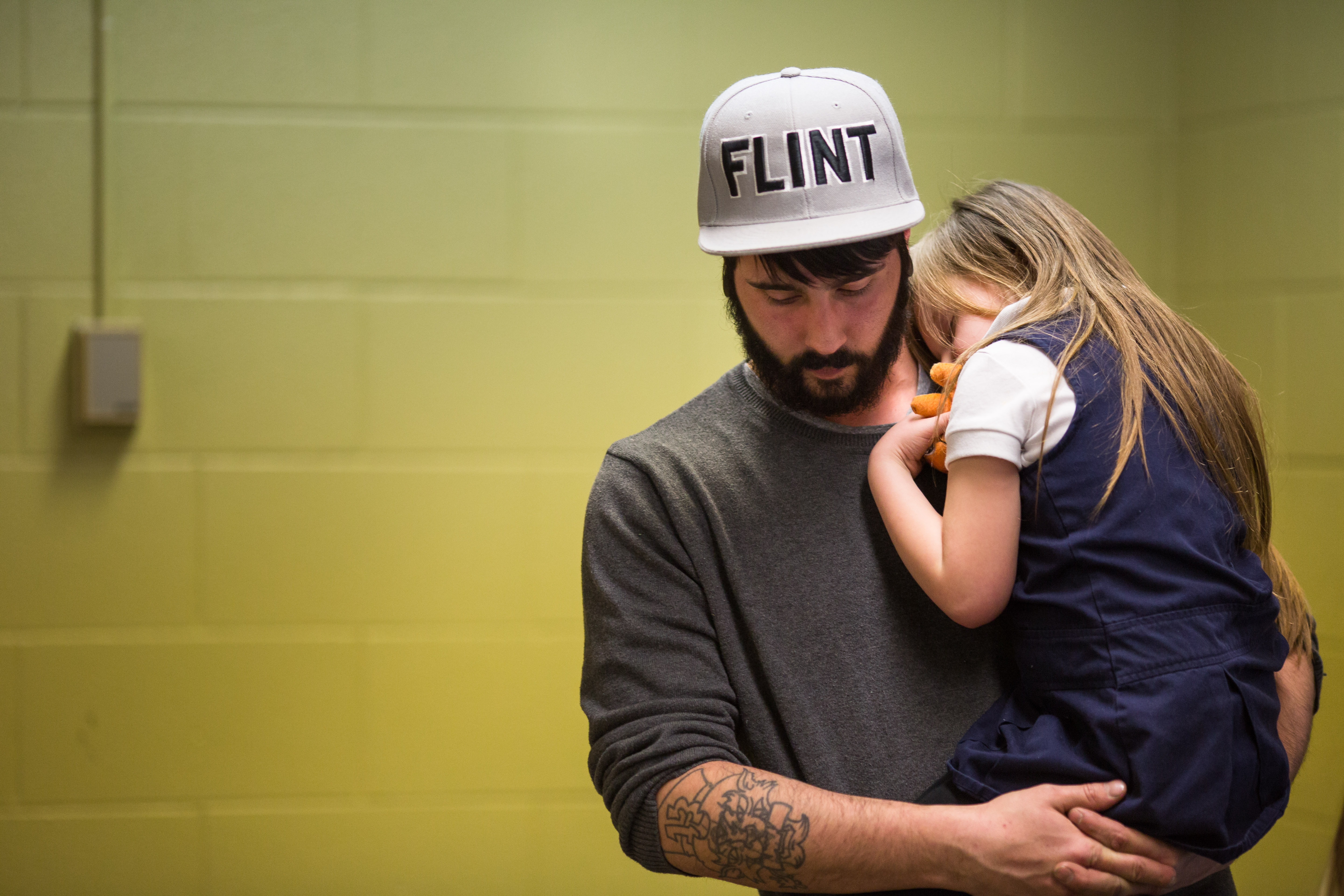 Matt Hopper holds his daughter after having her blood drawn to be tested for lead, in Flint, on Jan. 26, 2016.