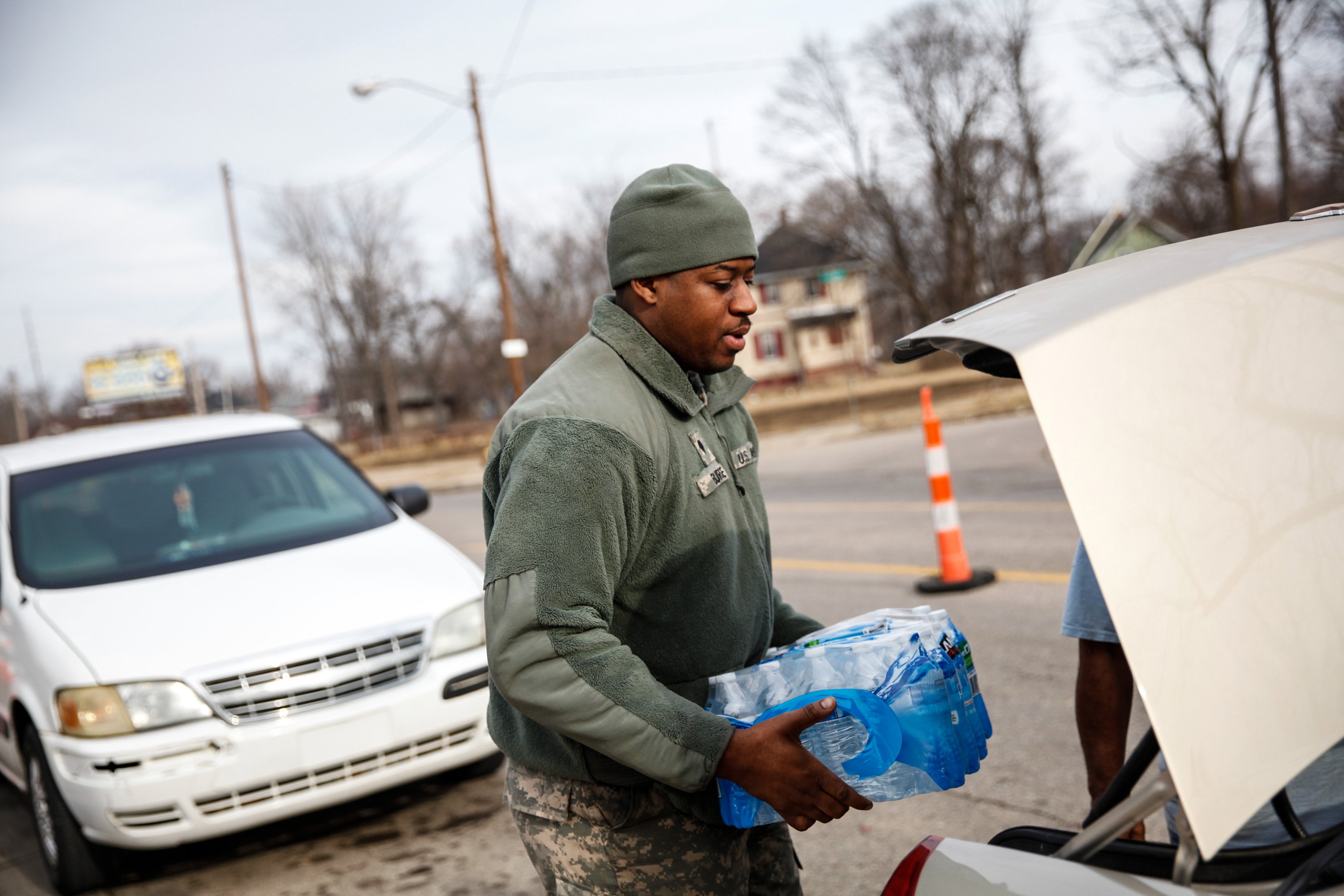 Army National Guard Spc. Terence Burse carries bottled water out to the car for a resident in Flint, Mich., on Feb. 7, 2016.
