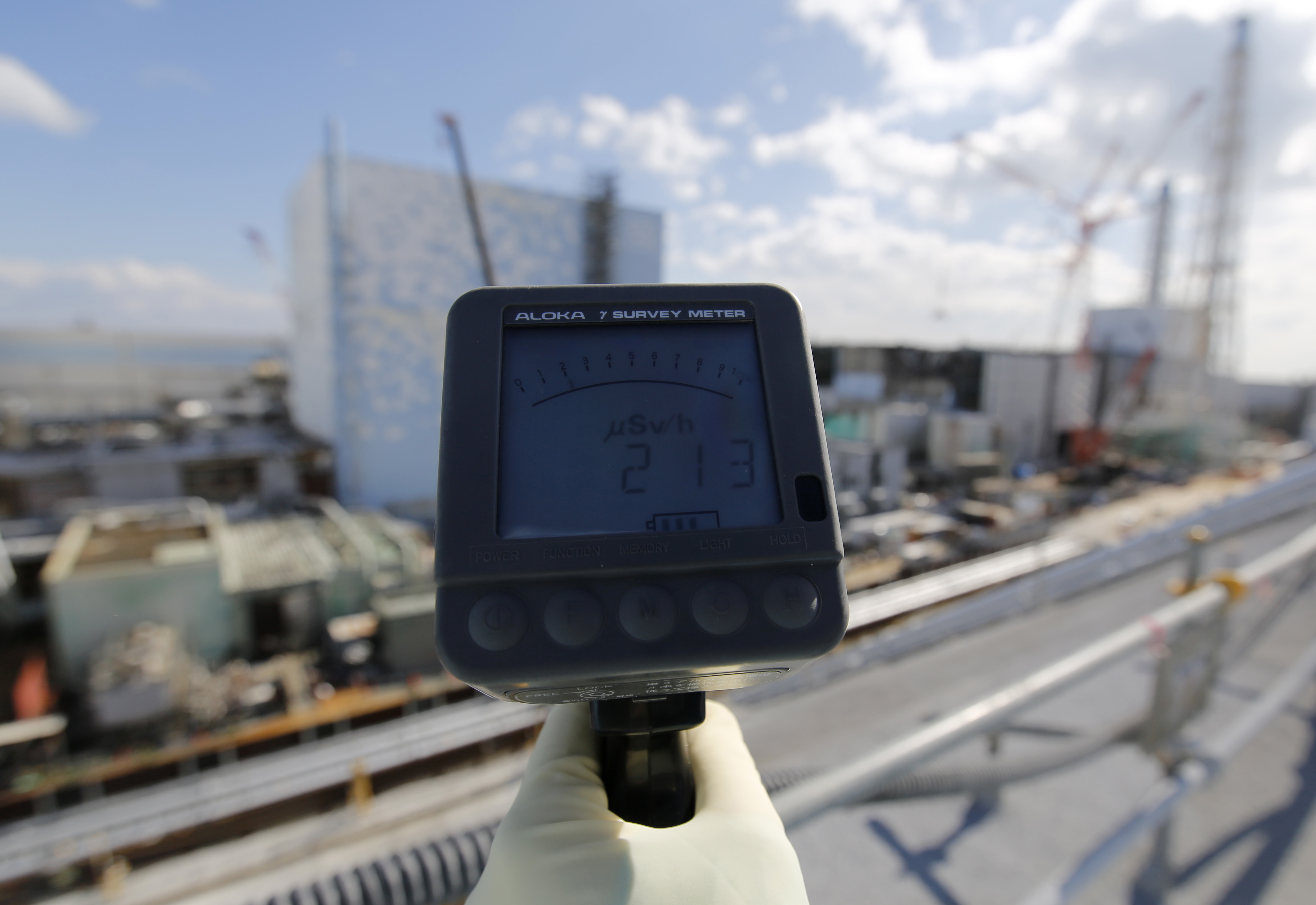 A Tokyo Electric Power Co. employee measures the radiation level at TEPCO's Fukushima Daiichi nuclear power plant in Okuma town on Feb. 10, 2016.