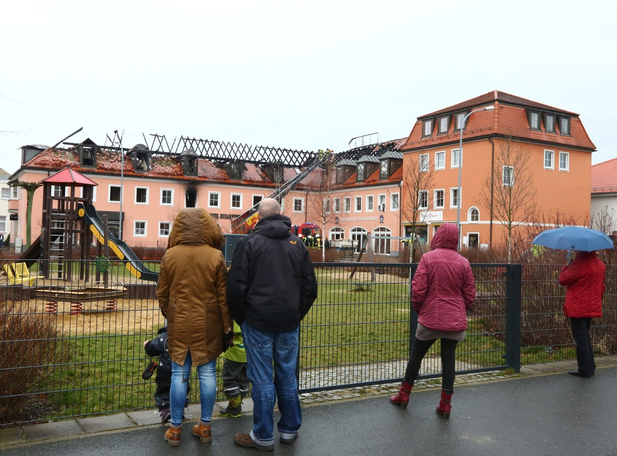People look at the burnt-out roof of a former hotel that was under reconstruction to become a shelter for migrants in Bautzen, Germany, Feb. 21, 2016.