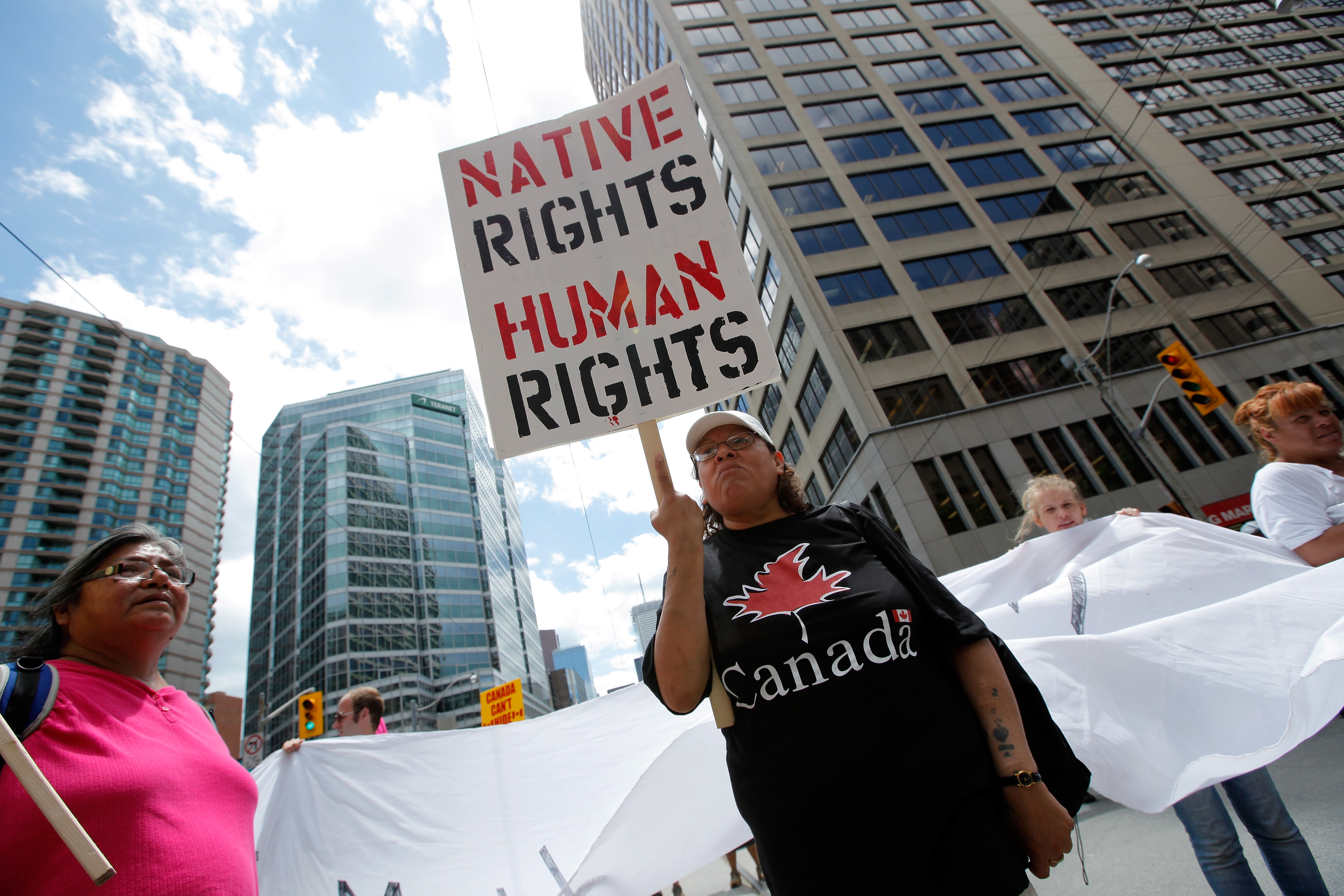 A woman holds a sign as several hundred indigenous people march through the streets of Toronto to bring attention to the plight of indigenous peoples in Canada on June 24, 2010