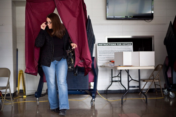 TOMS RIVER, NJ - NOVEMBER 06:  A woman exits a voting booth at Silver Bay Elementary School on November 6, 2012 in Toms River, New Jersey. The Elementary school, which usually hosts voting for two districts, accomodated voting for seven districts today, due damage caused by Superstorm Sandy. The entire voting system at the school is also run off generators, due to a loss of power.  (Photo by Andrew Burton/Getty Images)