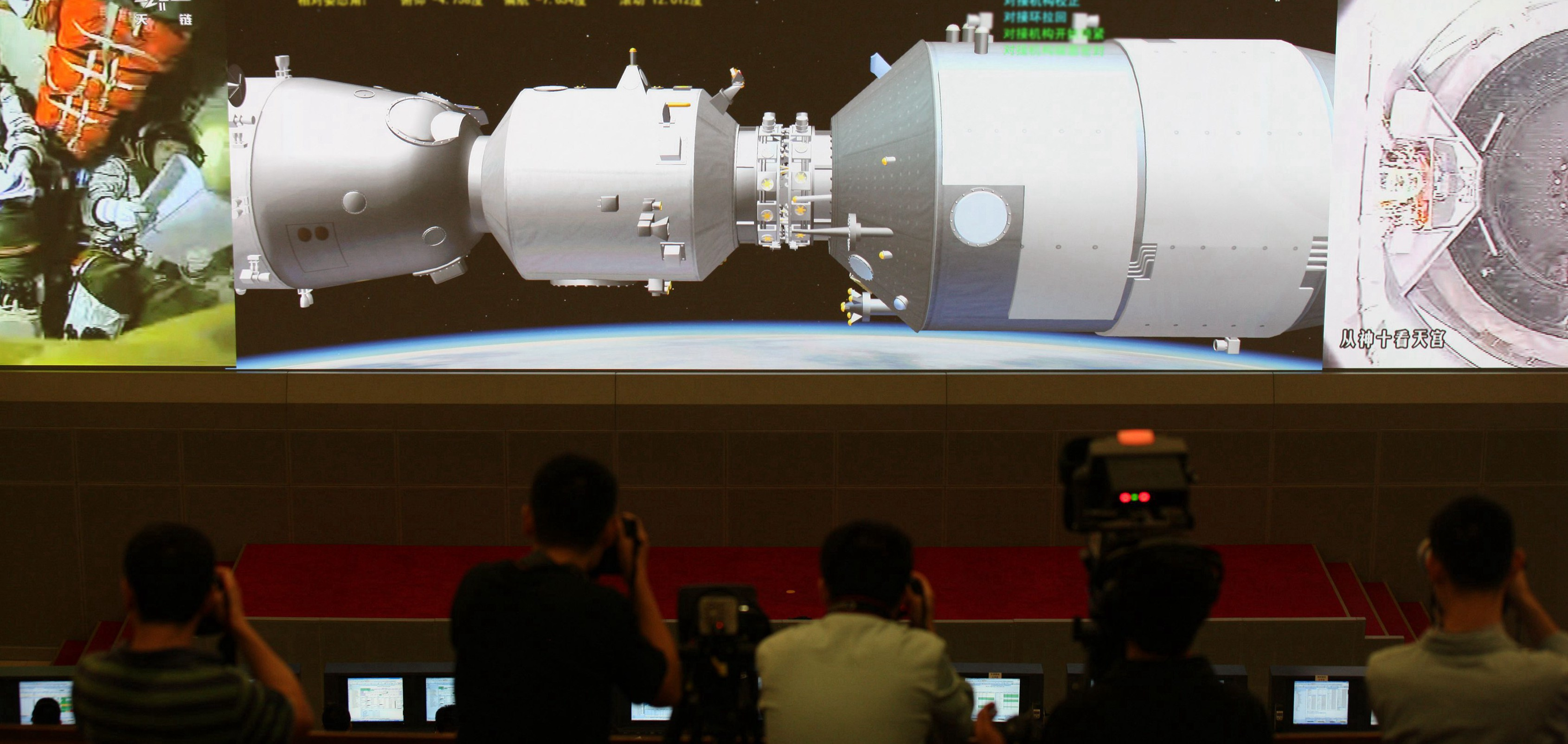 Scientists look at the screen showing the Shenzhou 10 manned spacecraft conducting docking with the orbiting Tiangong 1 space module at Beijing Aerospace Control Center on June 13, 2013, in Beijing