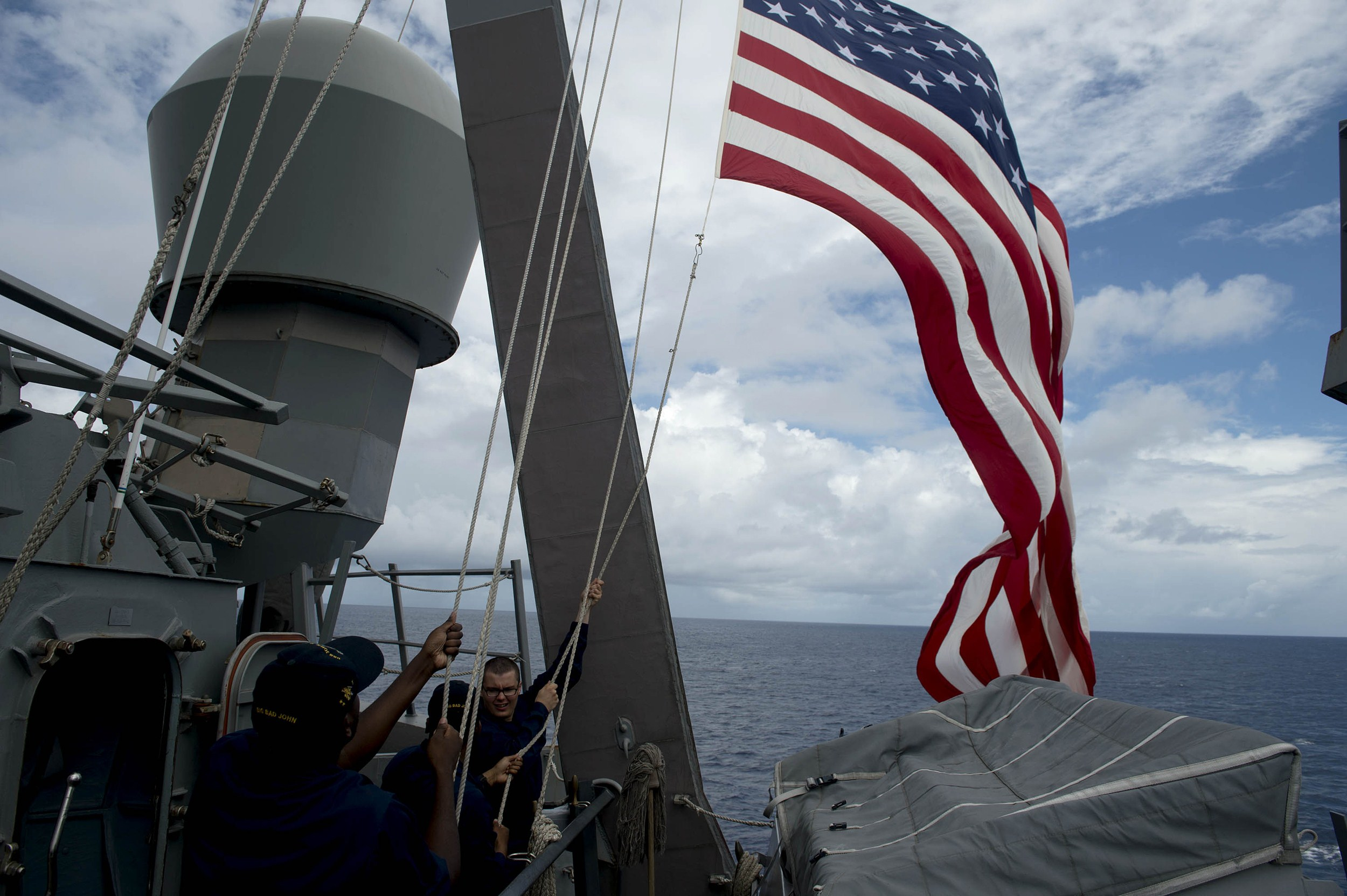U.S. Navy personnel aboard the U.S.S. John S. McCain raise their country's flag during a bilateral maritime exercise with the Philippine navy in the South China Sea near waters claimed by Beijing on June 28, 2014