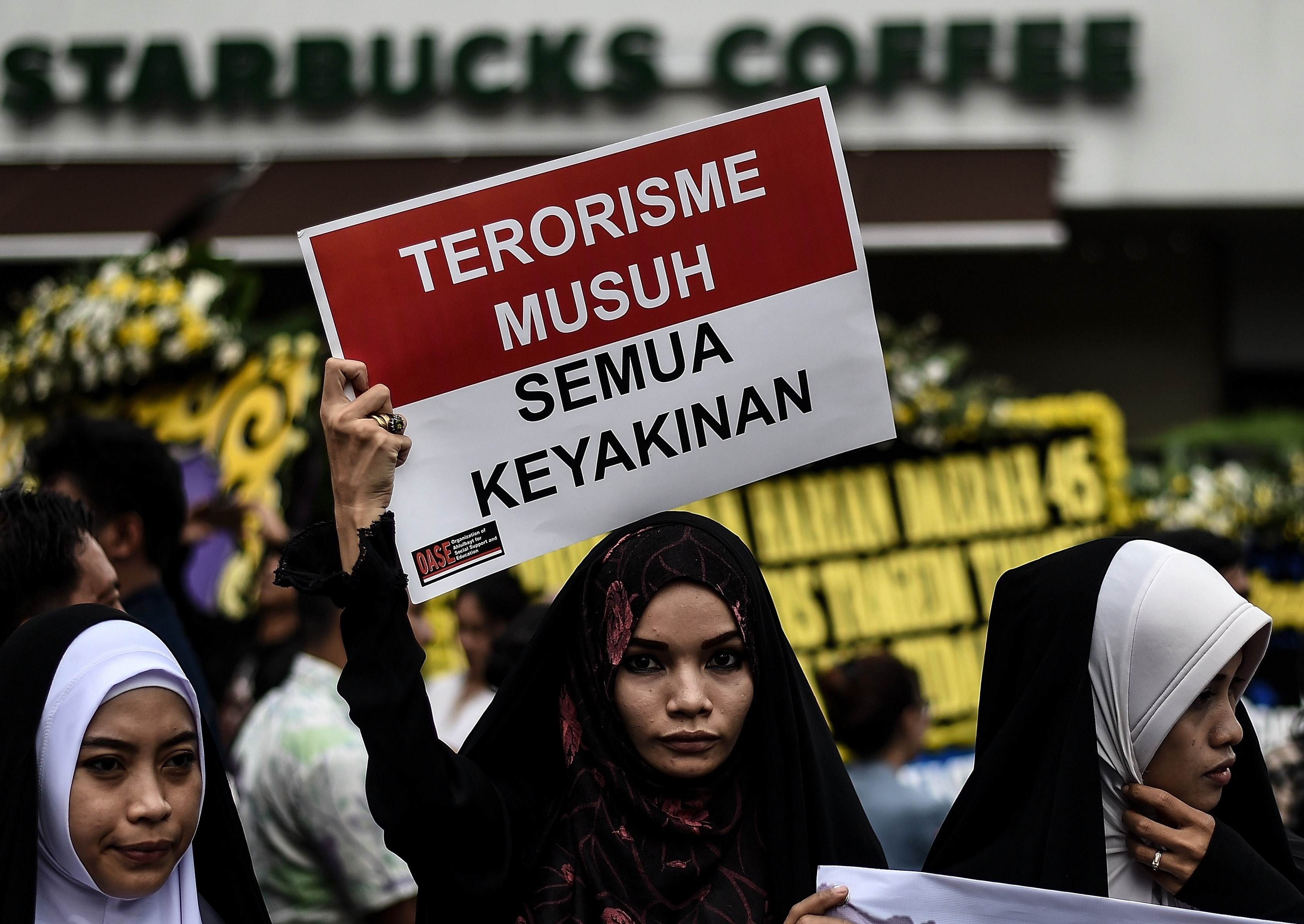 Women hold placards during a vigil outside the damaged Starbucks coffee shop in central Jakarta on Jan. 15, 2016, a day after a series of explosions hit the Indonesian capital