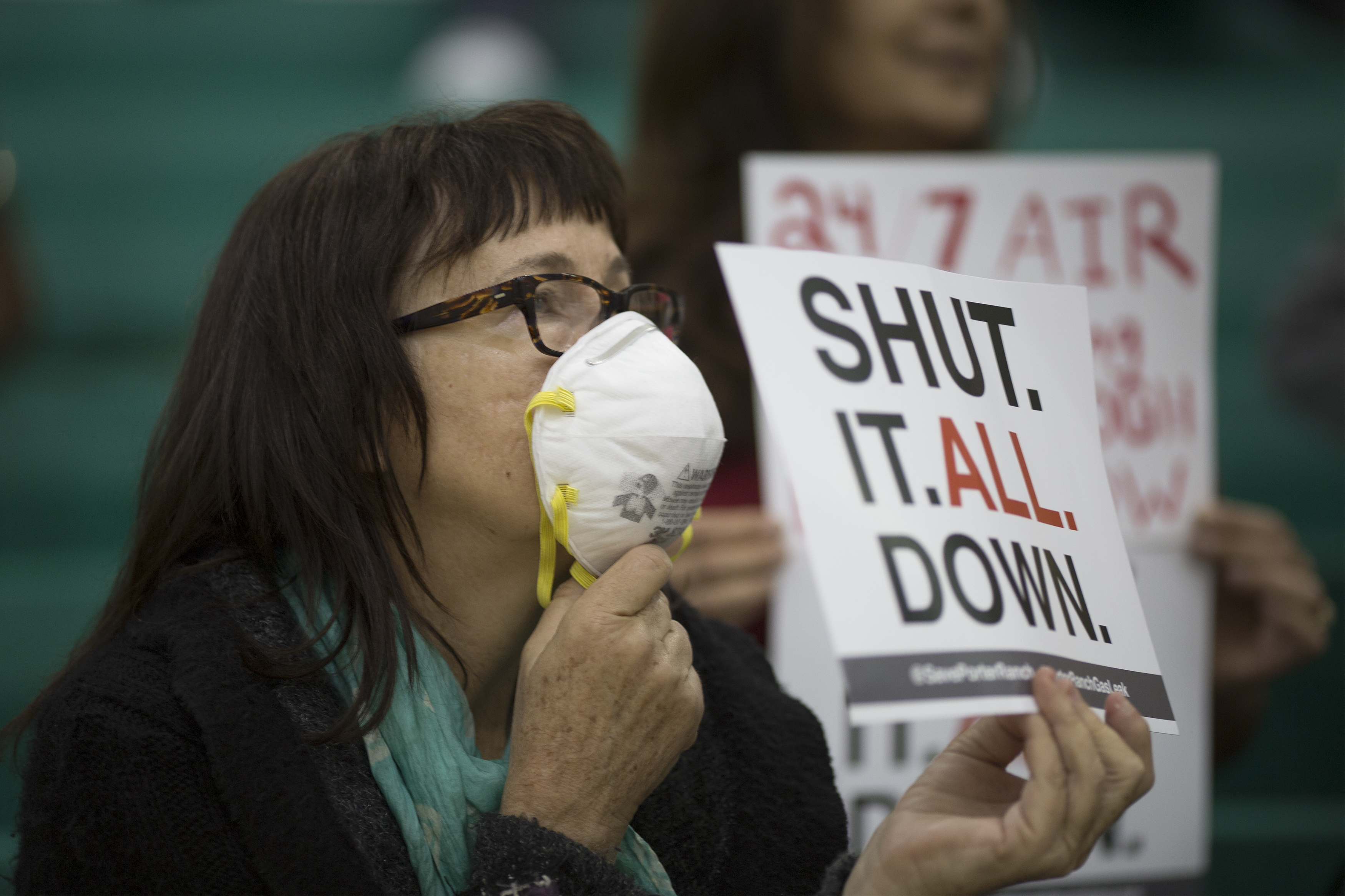 Sue Francis holds a sign while attending a public hearing before the South Coast Air Quality Management District (AQMD) regarding a proposed stipulated abatement order to stop a nearby massive natural gas leak, on January 16, 2016 in Granada Hills, near Porter Ranch, California.