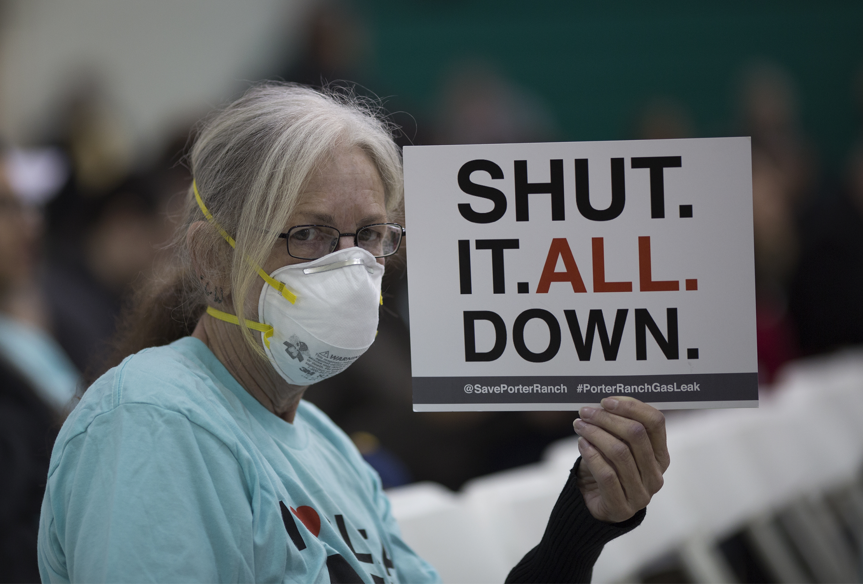 A woman holds a sign while attending a public hearing regarding an order to stop a nearby massive natural-gas leak, on Jan. 16, 2016, in Granada Hills, near Porter Ranch, Calif.