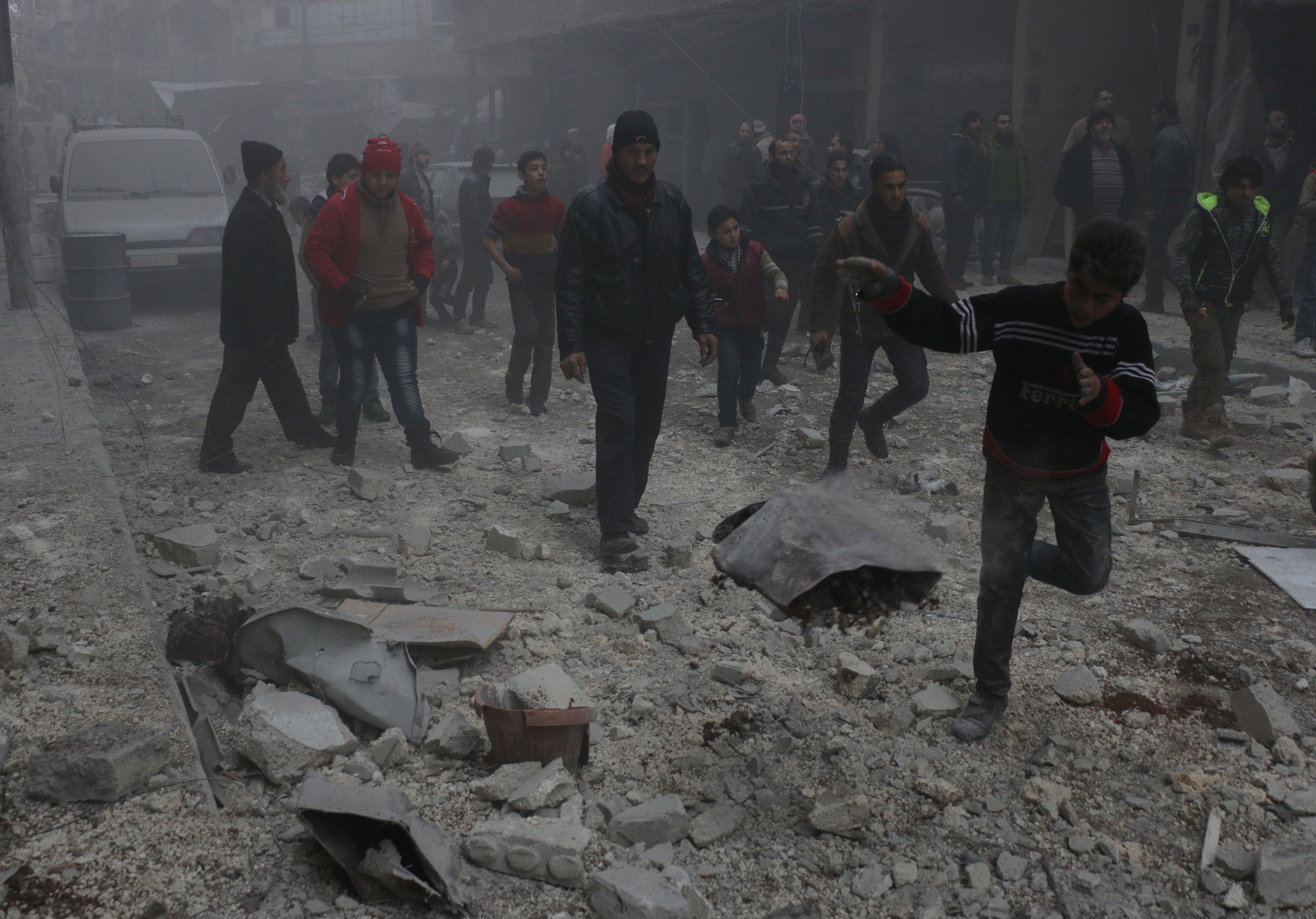 People are seen inside debris after a Russian forces staged air-strike over residential areas in Bustan al-Qasr neighborhood of Aleppo, Syria, on Jan. 21, 2016