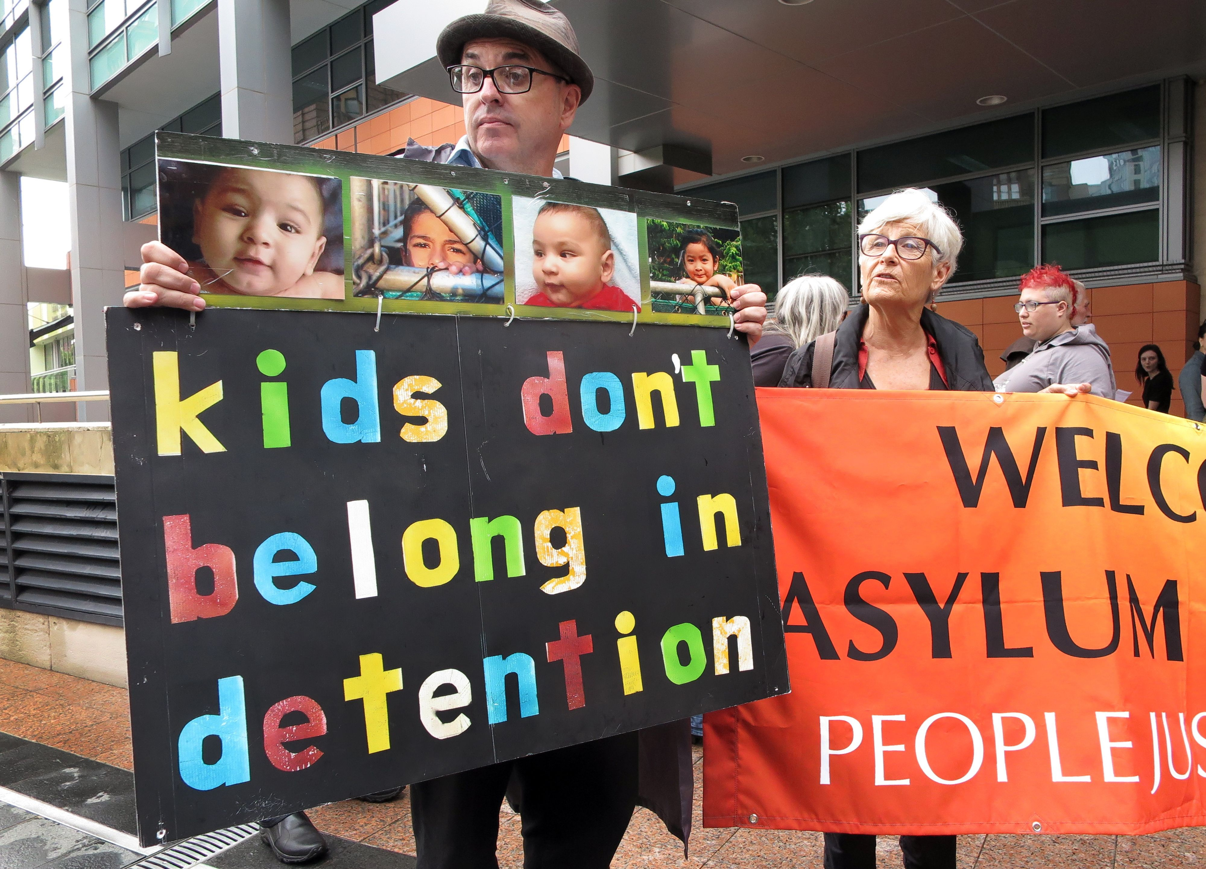 People hold placards at a protest outside an immigration office in Sydney on Feb. 4, 2016