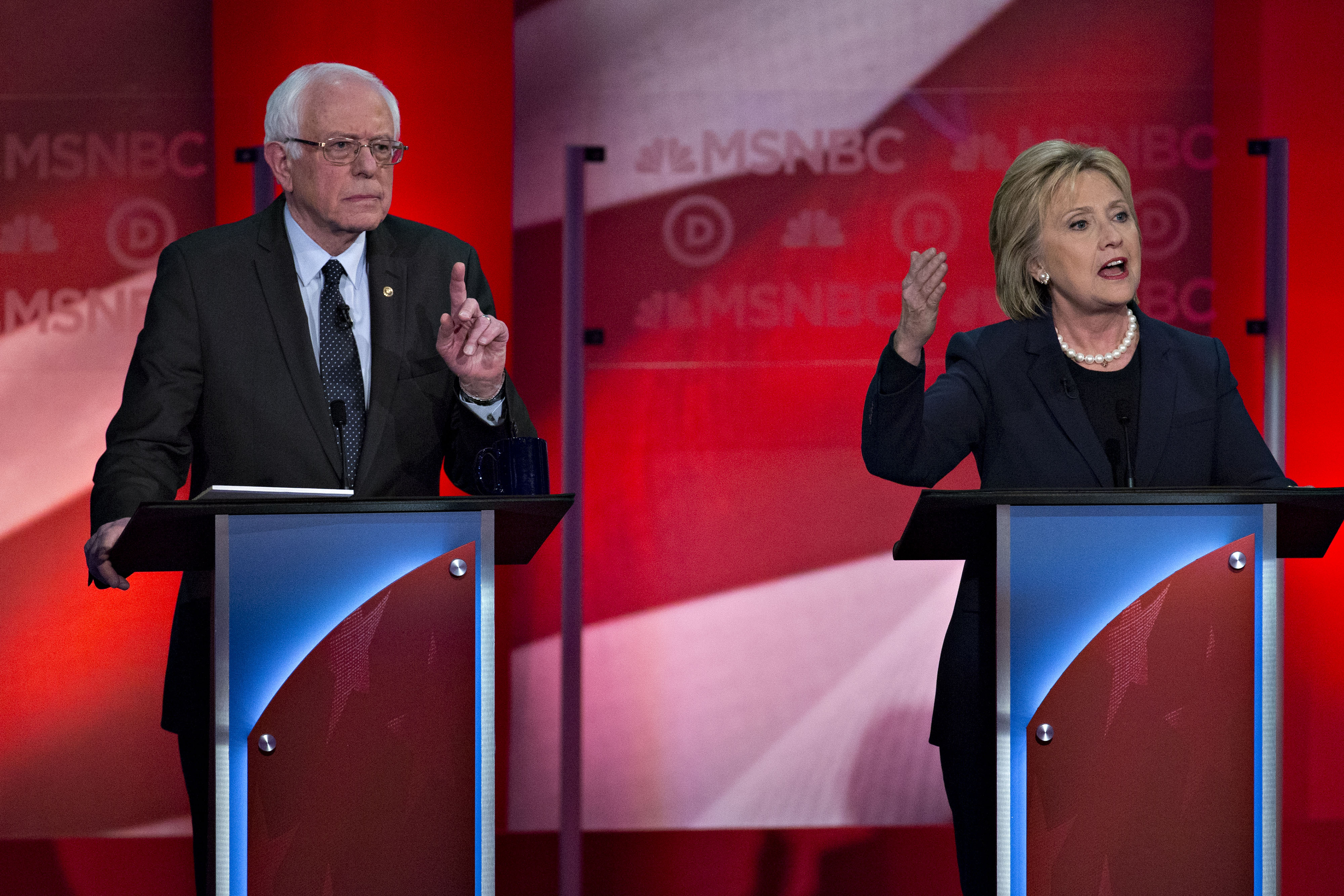 Hillary Clinton, former Secretary of State and 2016 Democratic presidential candidate, speaks as Senator Bernie Sanders, an independent from Vermont and 2016 Democratic presidential candidate, listens during the Democratic presidential candidate debate at the University of New Hampshire in Durham, N.H., on Feb. 4, 2016