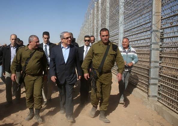 Israeli Prime Minister Benjamin Netanyahu (C) walks during a visit to the construction site of a new military border fence between Israel and Jordan, on February 9, 2016.                    Israel has begun construction on a security fence along its border with Jordan, the defence ministry announced, its latest such barrier intended to keep out illegal migrants and militants. The barrier will be 30 kilometres (19 miles) long between the resort city of Eilat and the site of the Sands of Samar and will cost 300 million shekels ($75 million, 70 million euros), according Israeli authorities. / AFP / POOL / MARC ISRAEL SELLEM        (Photo credit should read MARC ISRAEL SELLEM/AFP/Getty Images)