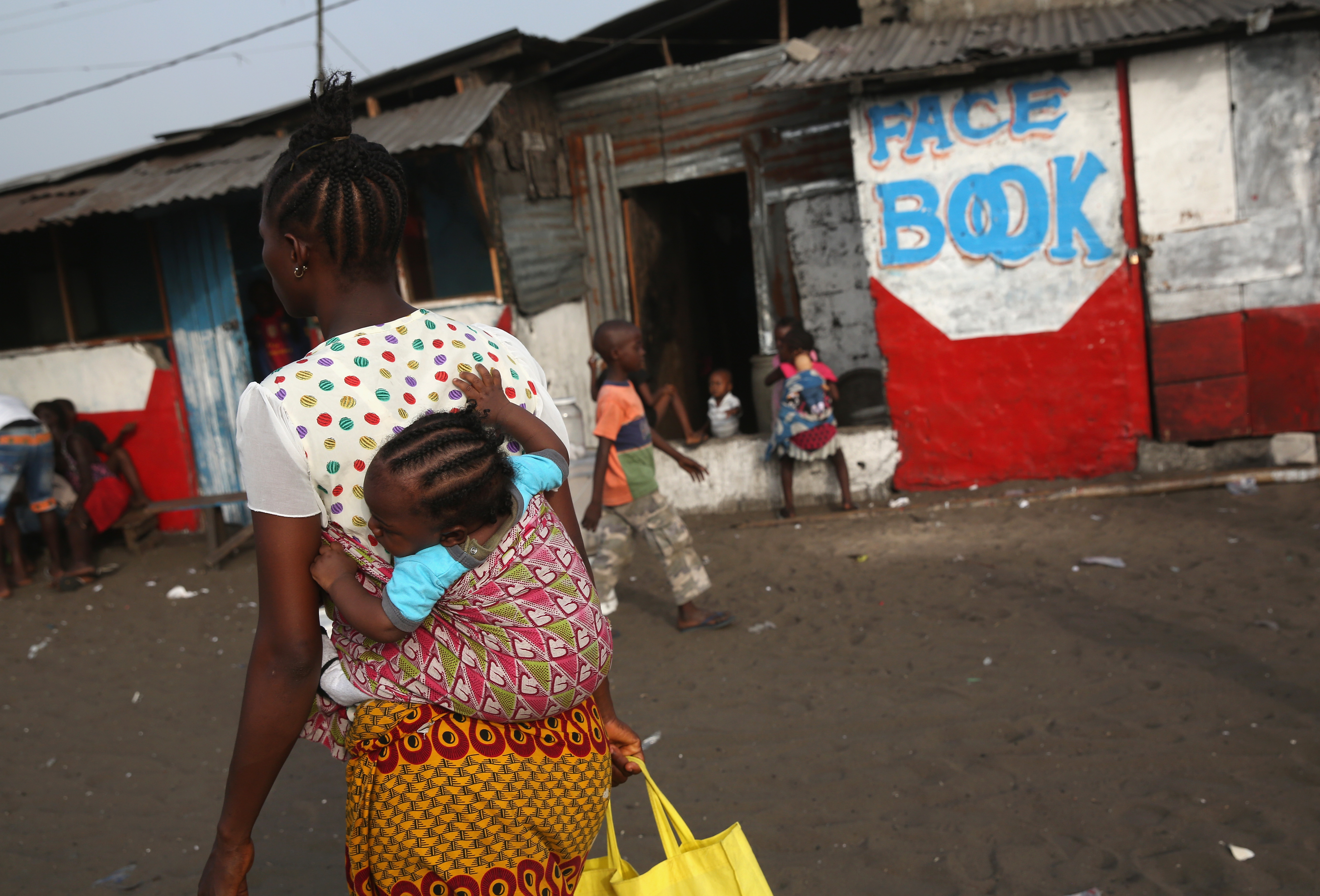 A woman and her child pass by an Internet café in the West Point slum on Feb. 9, 2016, in Monrovia, Liberia