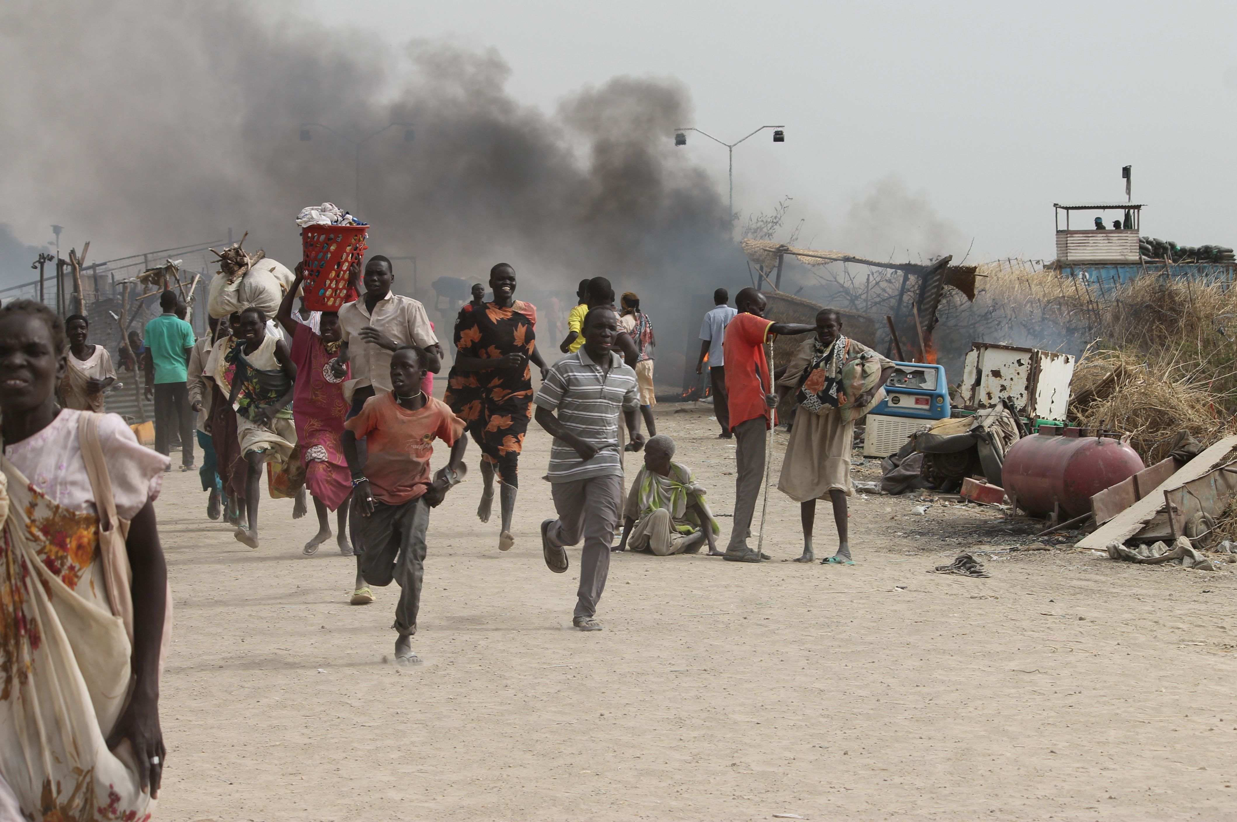 Sudanese civilians flee fighting in an U.N. base in the northeastern town of Malakal on February 18, 2016, where gunmen opened fire on civilians