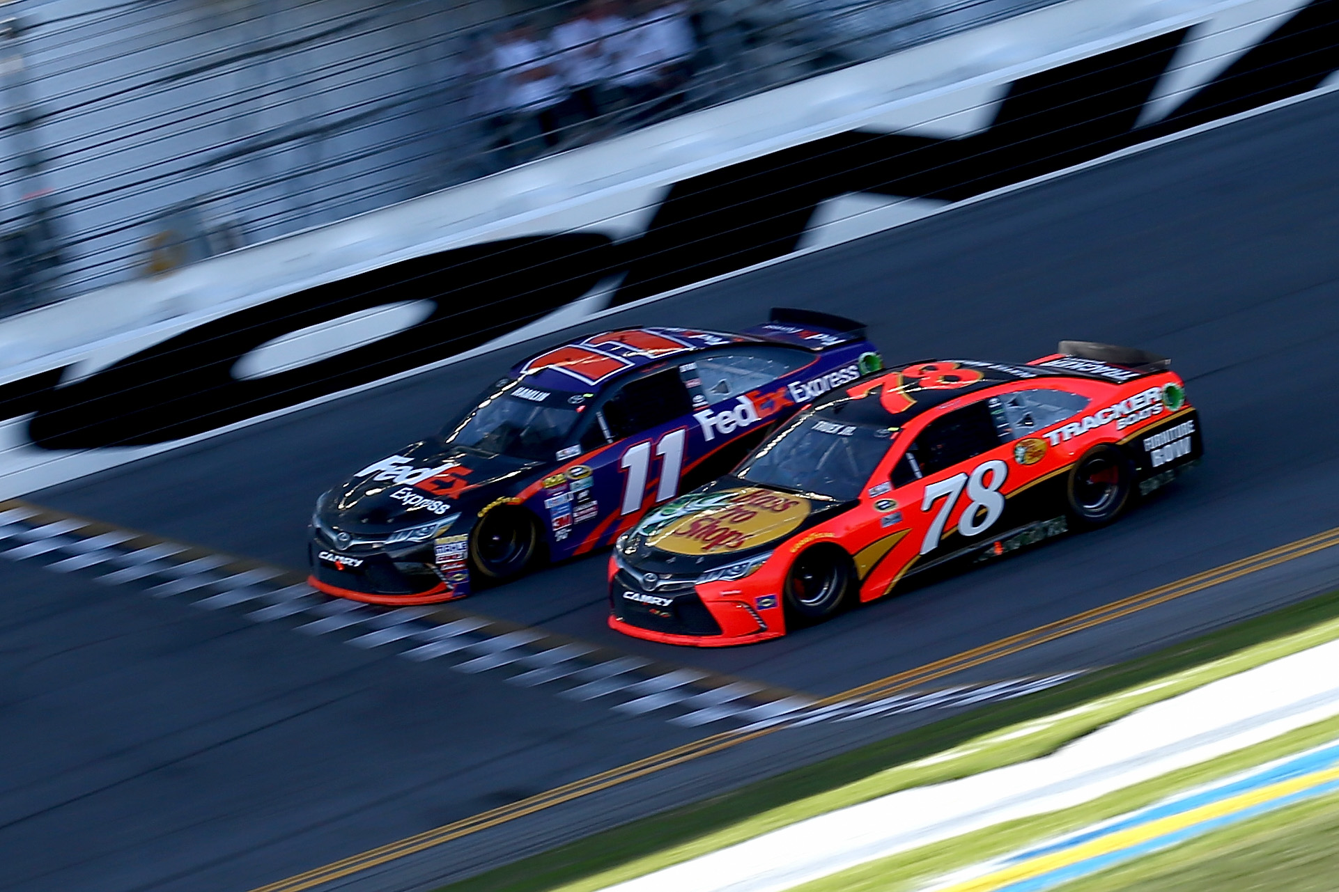 Denny Hamlin, driver of the #11 FedEx Express Toyota, takes the checkered flag ahead of Martin Truex Jr., driver of the #78 Bass Pro Shops/Tracker Boats Toyota, to win the NASCAR Sprint Cup Series Daytona 500 on Feb. 21, 2016 in Daytona Beach, Fla.