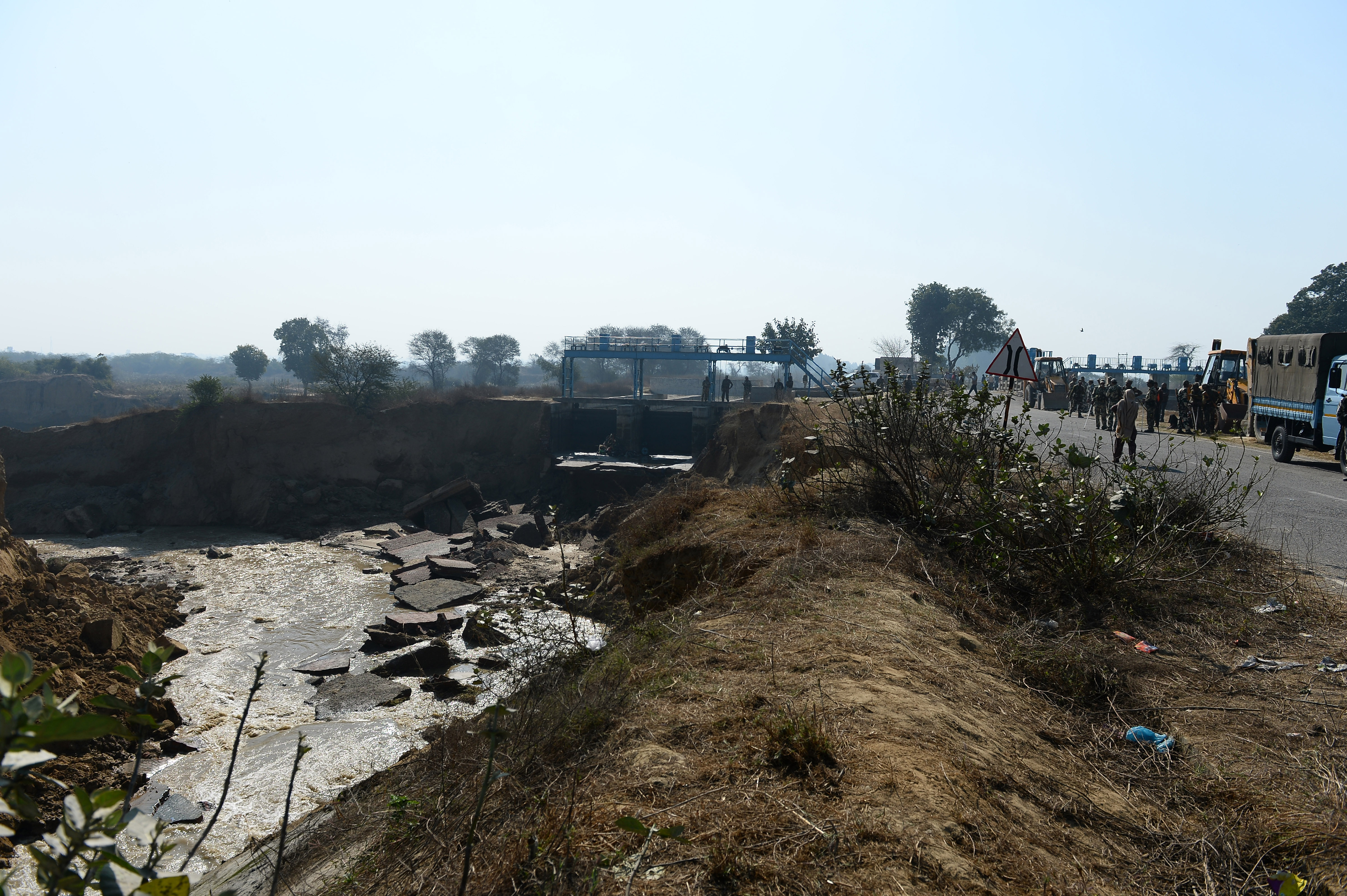 Indian soldiers stand near a damaged portion of the Munak canal, which supplies water to New Delhi, near Bindroli village in the Indian state of Haryana, on Feb. 22, 2016