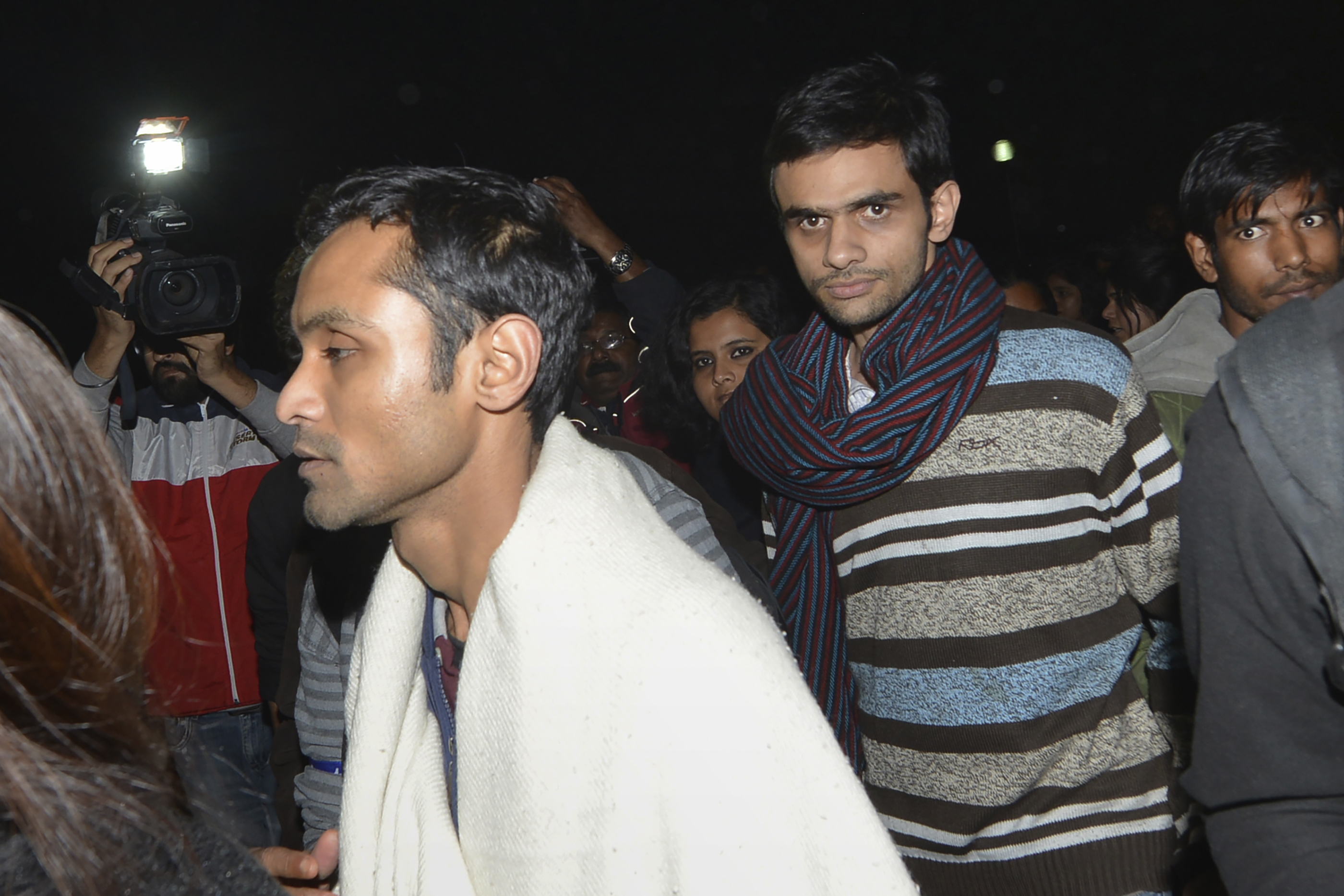 Indian student activists Umar Khalid, center, and Anirban Bhattacharya walk through the campus of New Delhi's Jawaharlal Nehru University on Feb. 23, 2016