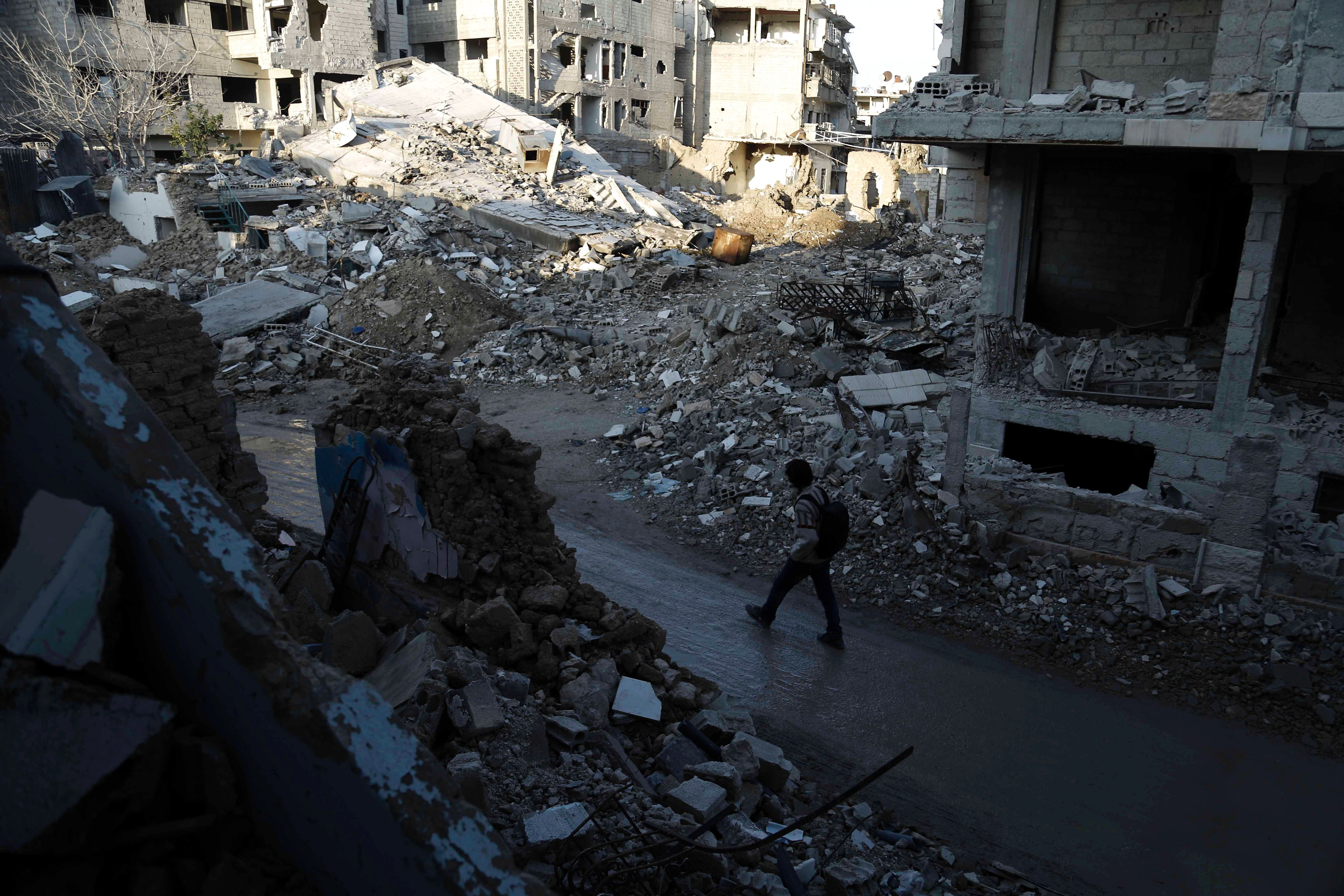 Syrian man walks along a street damaged by shelling in the neighborhood of Jobar, on the eastern outskirts of the capital Damascus, on Feb. 24, 2016