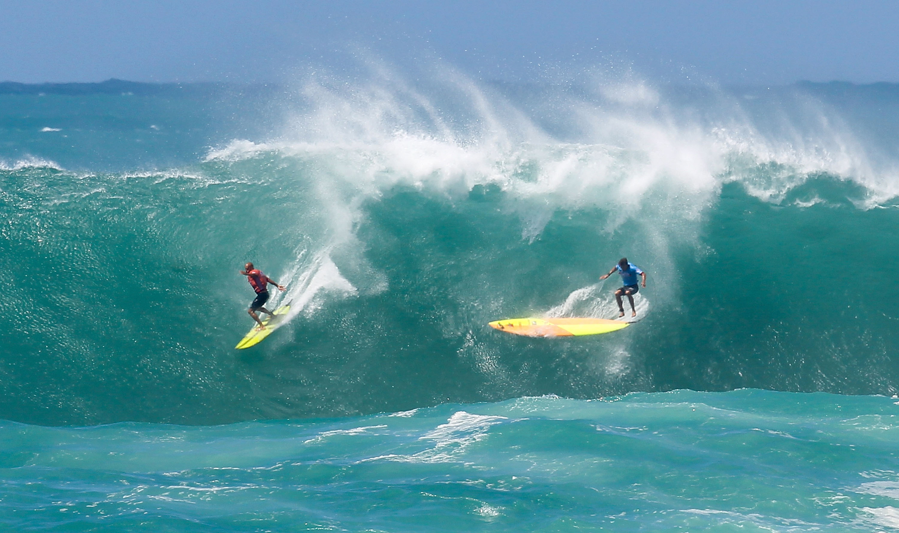 Professional surfer Ramon Navarro (L) makes the drop on a wave while professional surfer Jamie Mitchell loses control and wipes out at Waimea Bay on Feb. 25, 2016 in Waimea, Hawaii.