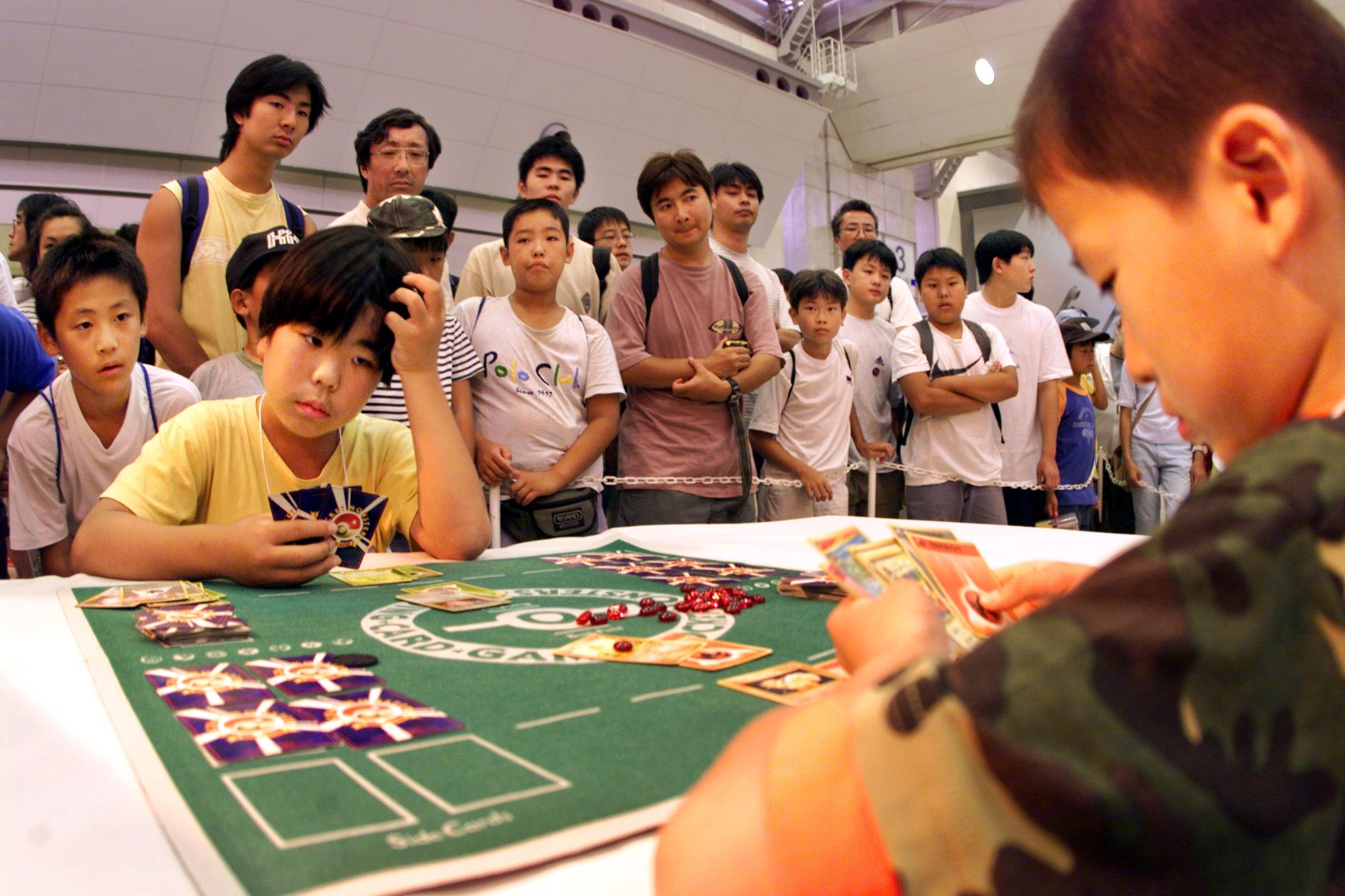 A crowd watches as Japanese boys play a close game in Tokyo 04 August 1999 as they participate in a Pokemon (Pocket Monster) card game tournament.