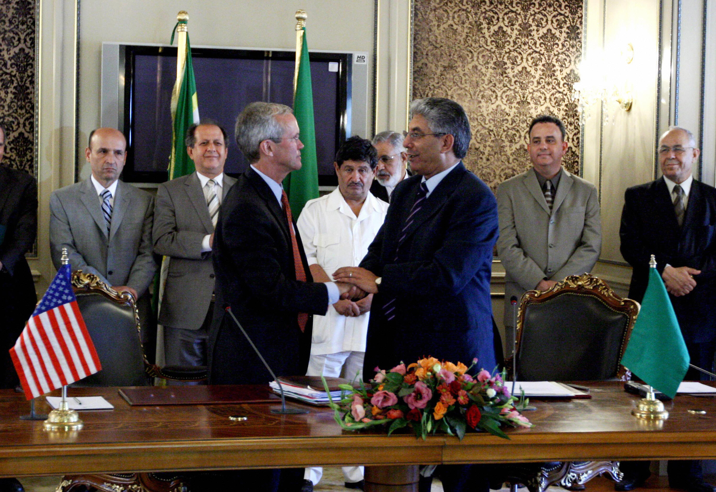 US Assistant Secretary of State for Near Eastern affairs David Welch (L), and Libyan Deputy Foreign Minister Ahmad Fitouri (R) shake hands after the signing of a compensation agreement between their two countries pertaining to the victims of past Libyan-US conflict in Tripoli on Aug. 14, 2008. See slide 5 above for Taryn Simon's interpretation.