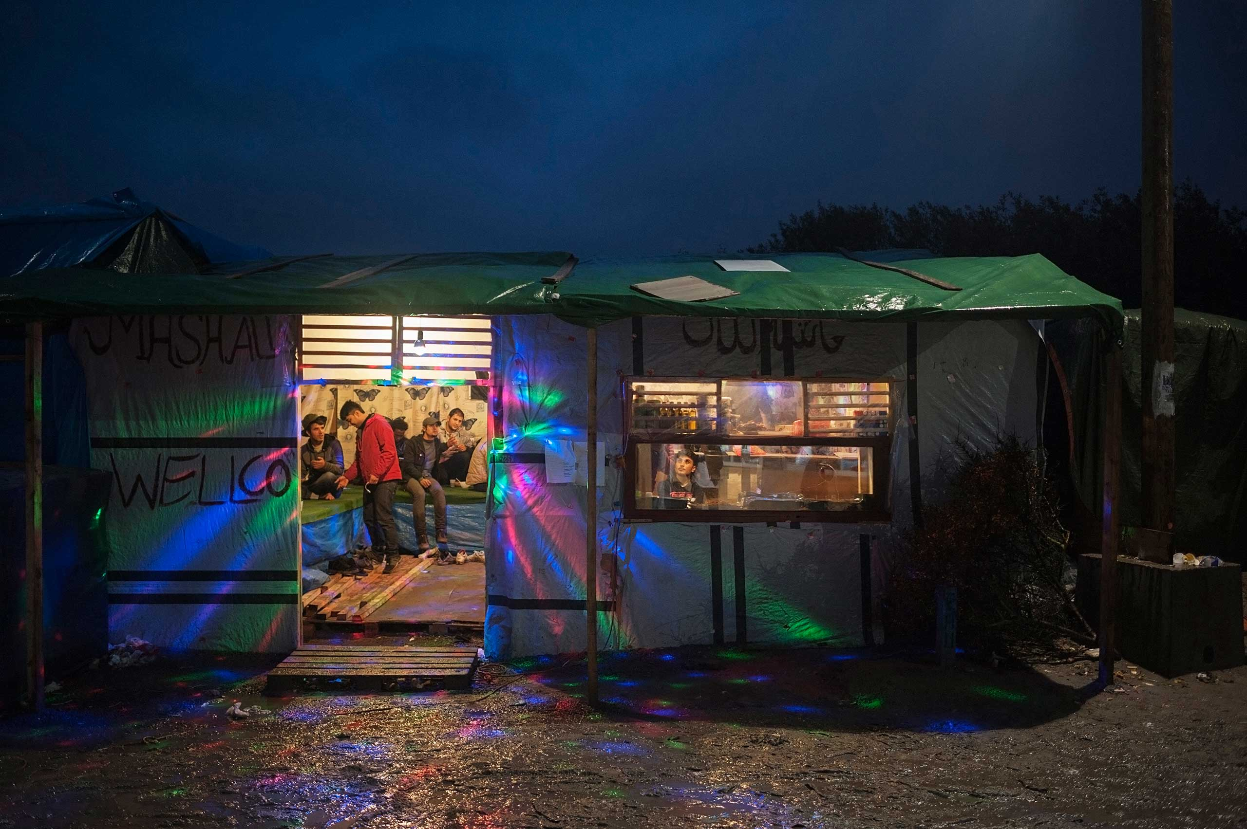 People chat in a Afghan Bar-Shop at the entrance of the so called Jungle in Calais, France on Nov. 6, 2015.