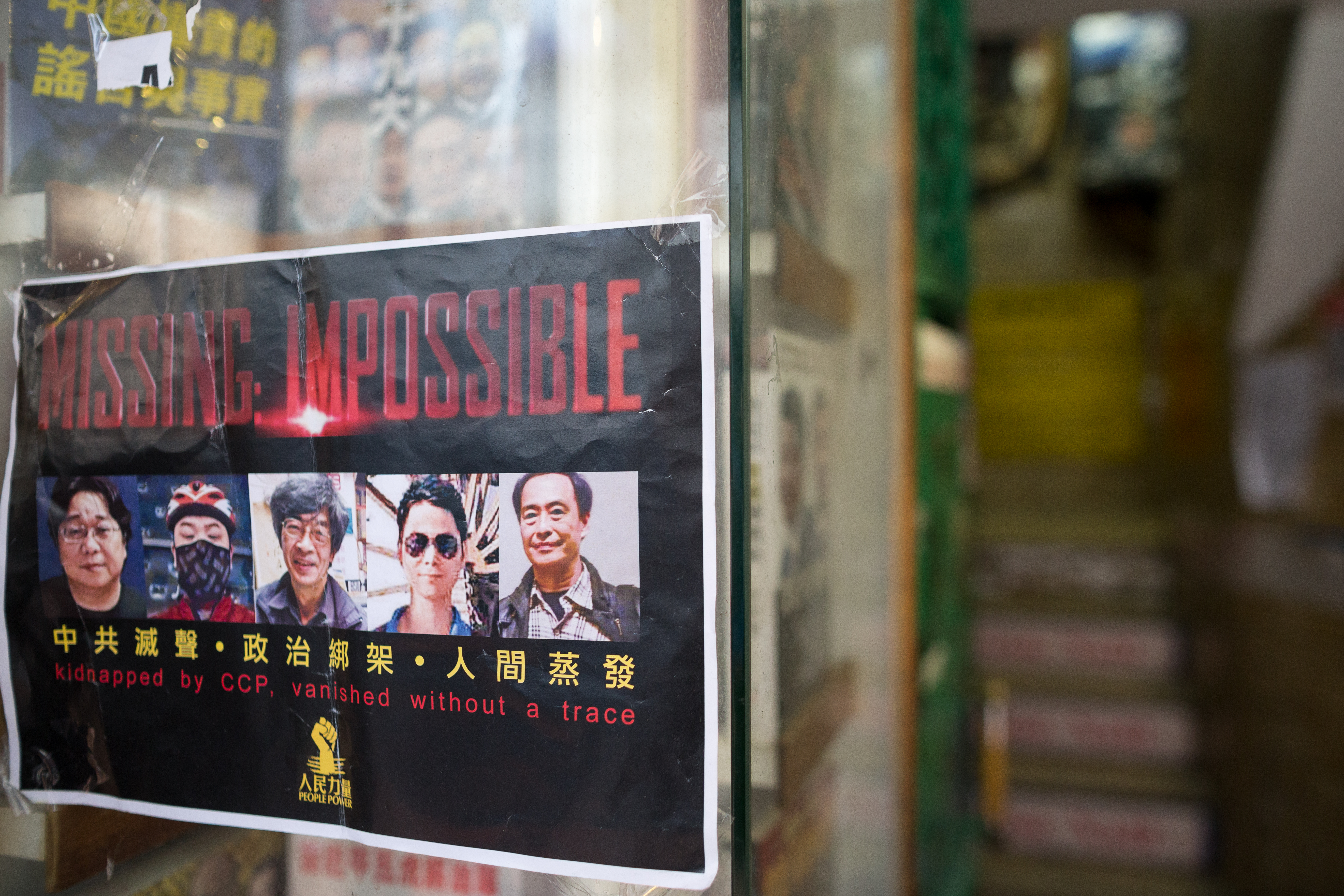 A flyer with photos of five Hong Kong booksellers hangs on the entrance to Causeway Bay Books shop in Hong Kong on Feb. 5, 2016