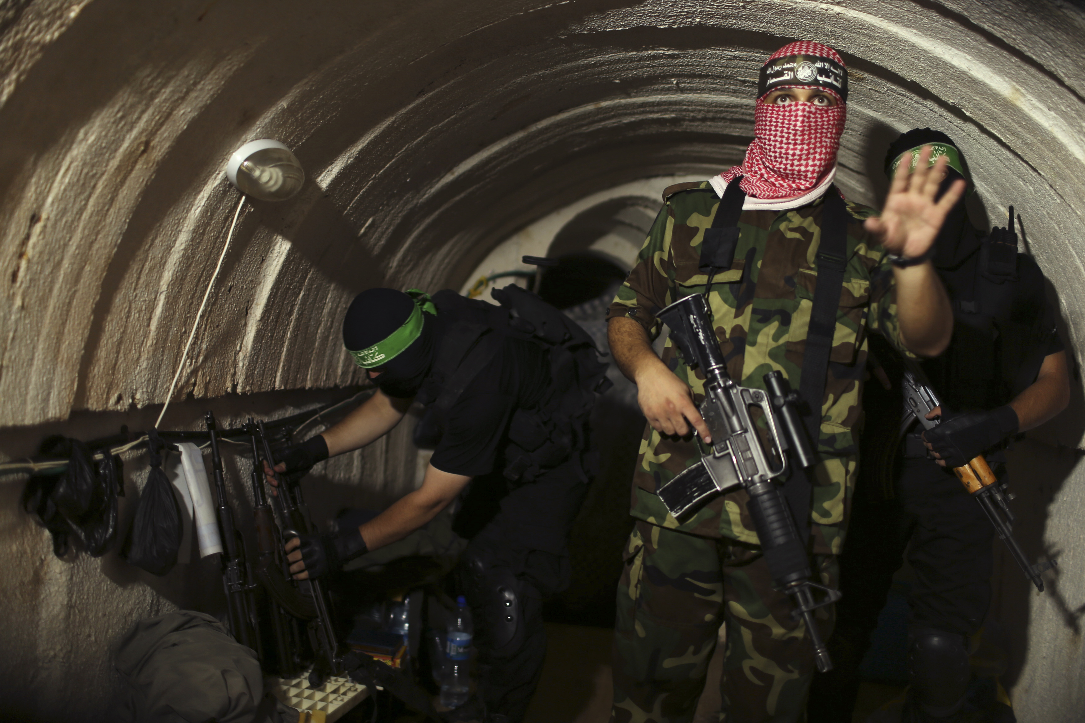 A Palestinian fighter from the Izz el-Deen al-Qassam Brigades, the armed wing of the Hamas movement, gestures inside an underground tunnel in Gaza Aug, 18, 2014.