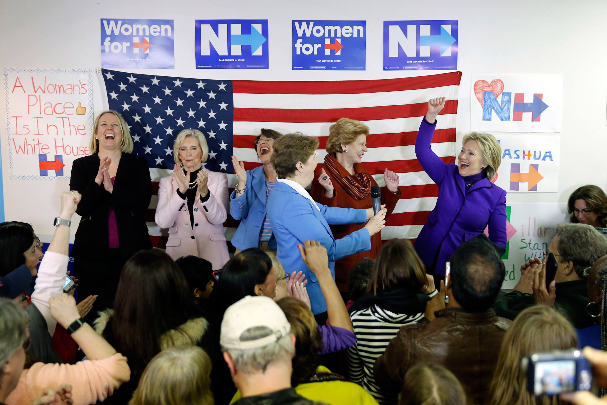 Hillary Clinton is joined on stage by EMILY's List President Stephanie Schriock, left, Lily Ledbetter, Sen. Amy Klobuchar, D-Minn., Jeanne Shaheen, D-N.H., and Sen. Debbie Stabenow, D-Mich., during a visit to a campaign office in Nashua, N.H., on Feb. 5, 2016.