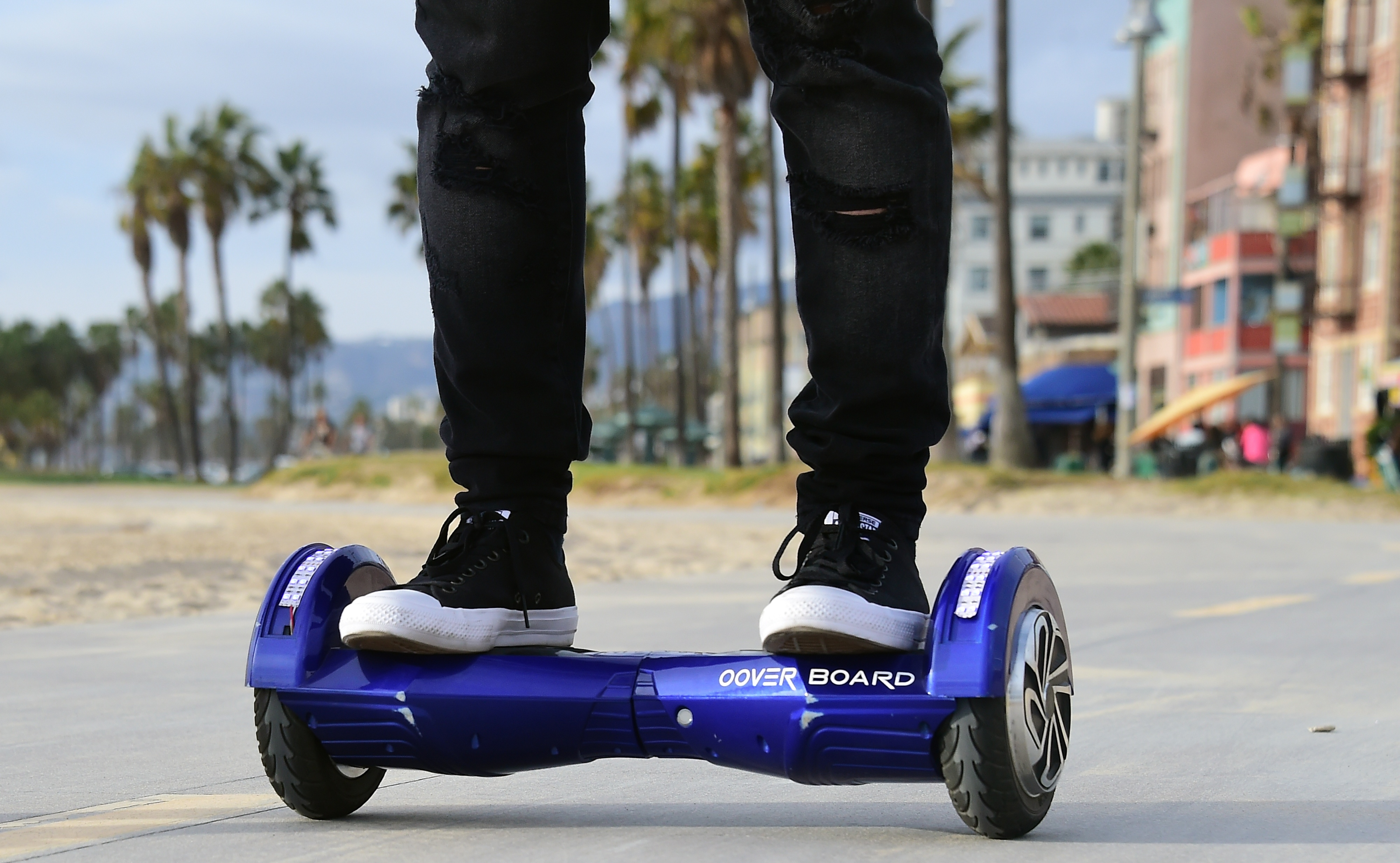Michael Tran uses his hoverboard on the Venice Beach Boardwalk on December 10, 2015.
