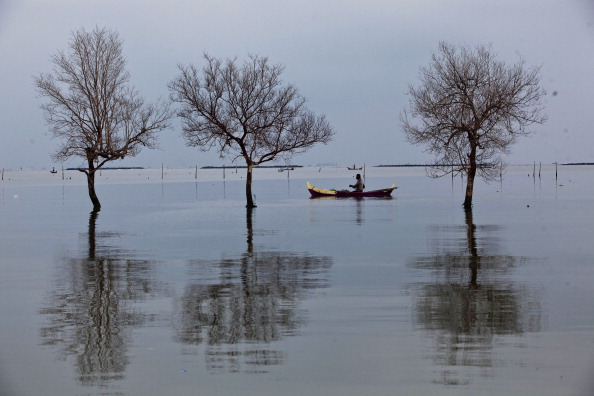 A fisherman in flood waters from rising sea levels in Demak, Central Java, Indonesia, on Dec. 12, 2013.