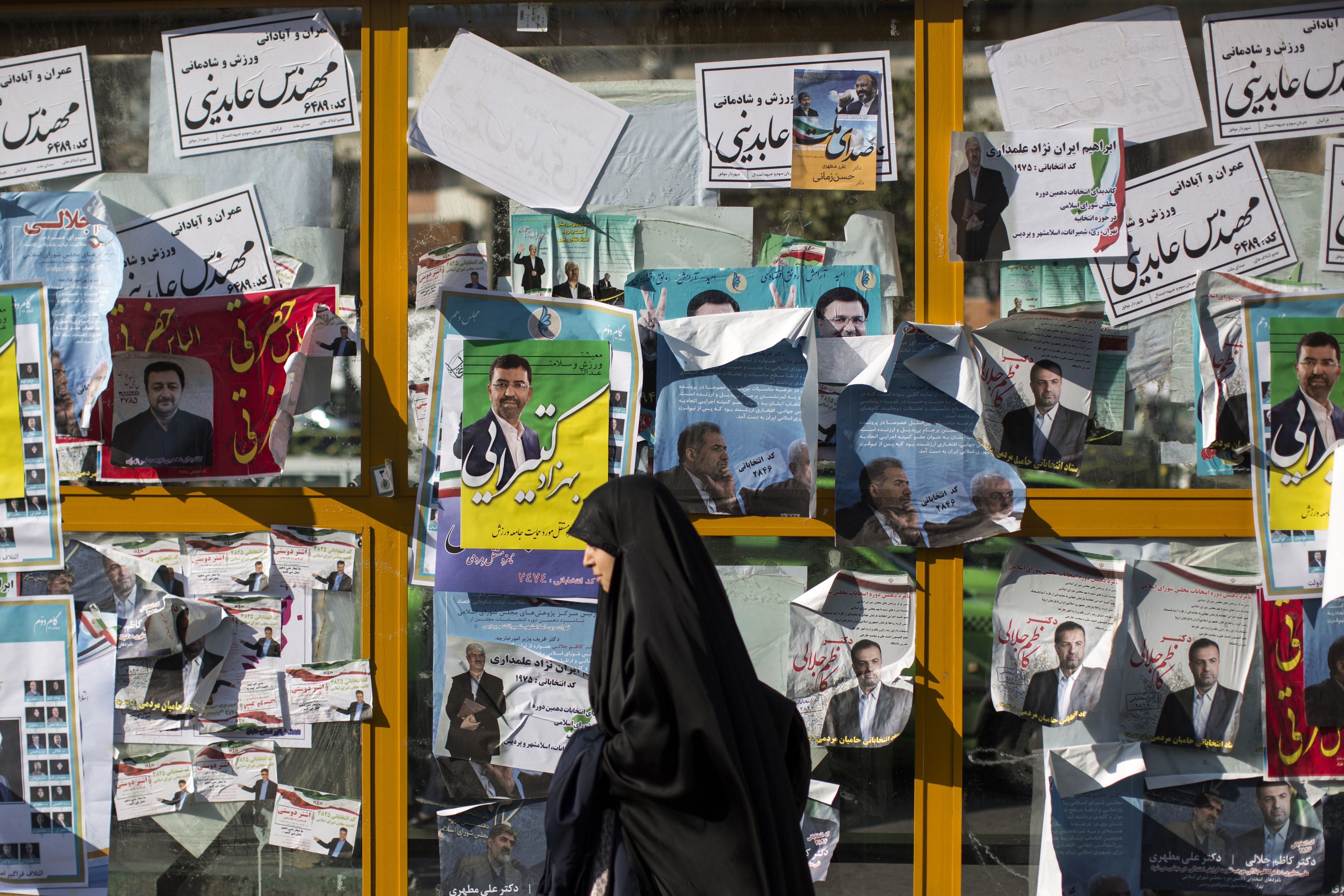An Iranian woman walks past electoral posters for upcoming parliamentary elections in downtown Tehran on Feb. 25, 2016.