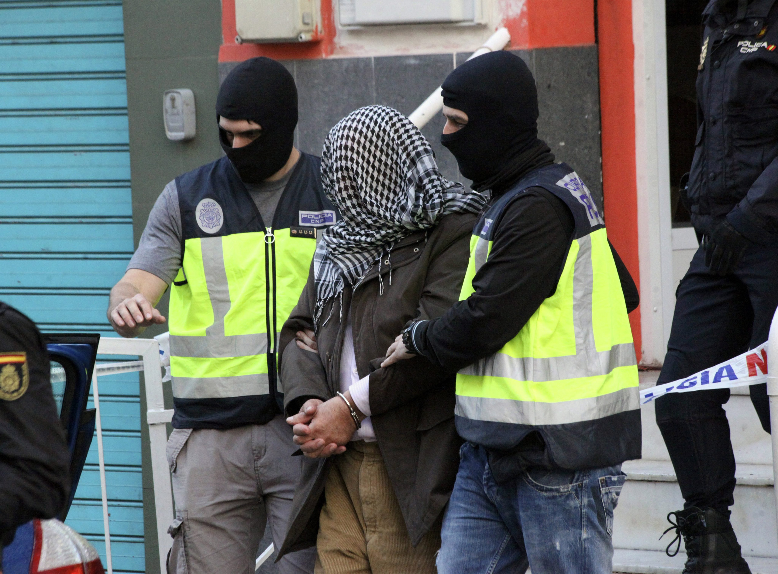 Spanish policemen escort a man who was arrested during a operation against Jihadist terrorism in Ceuta, Spanish enclave in northern Africa, on Feb. 7, 2016.
