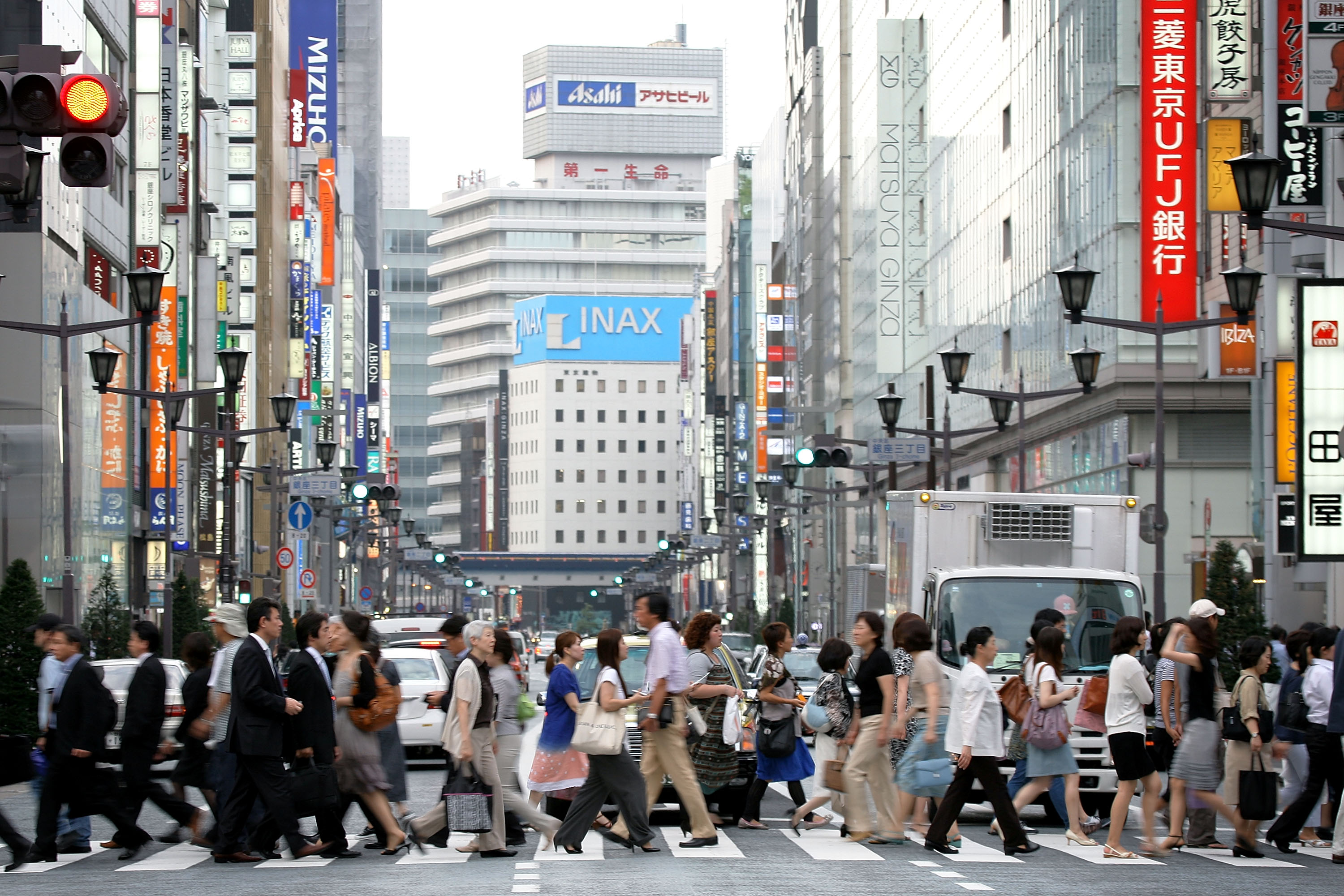 People walk across the street in the Ginza district on July 10, 2009 in Tokyo, Japan.