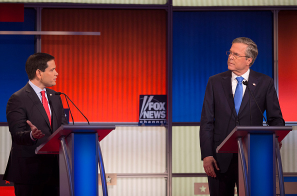 Republican Presidential candidate Florida Senator Marco Rubio (L) speaks as former Florida Gov. Jeb Bush looks on during the Republican Presidential debate sponsored by Fox News at the Iowa Events Center in Des Moines, Iowa on January 28, 2016.