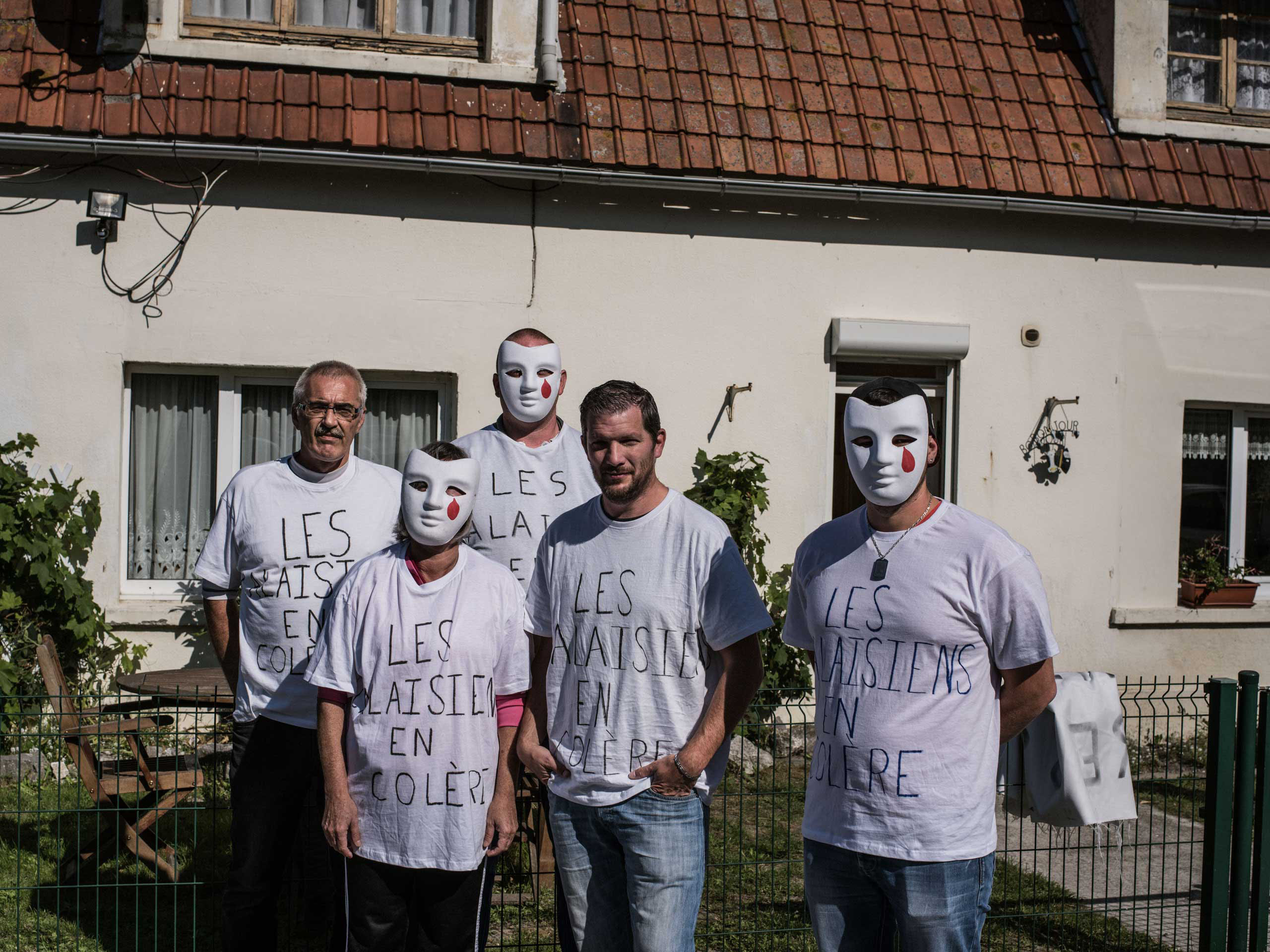 A group of neighbors wear tee-shirts proclaiming   Angry Calaisiens,  while protesting the migrant camp known as the  jungle,  Sept. 11, 2015.
