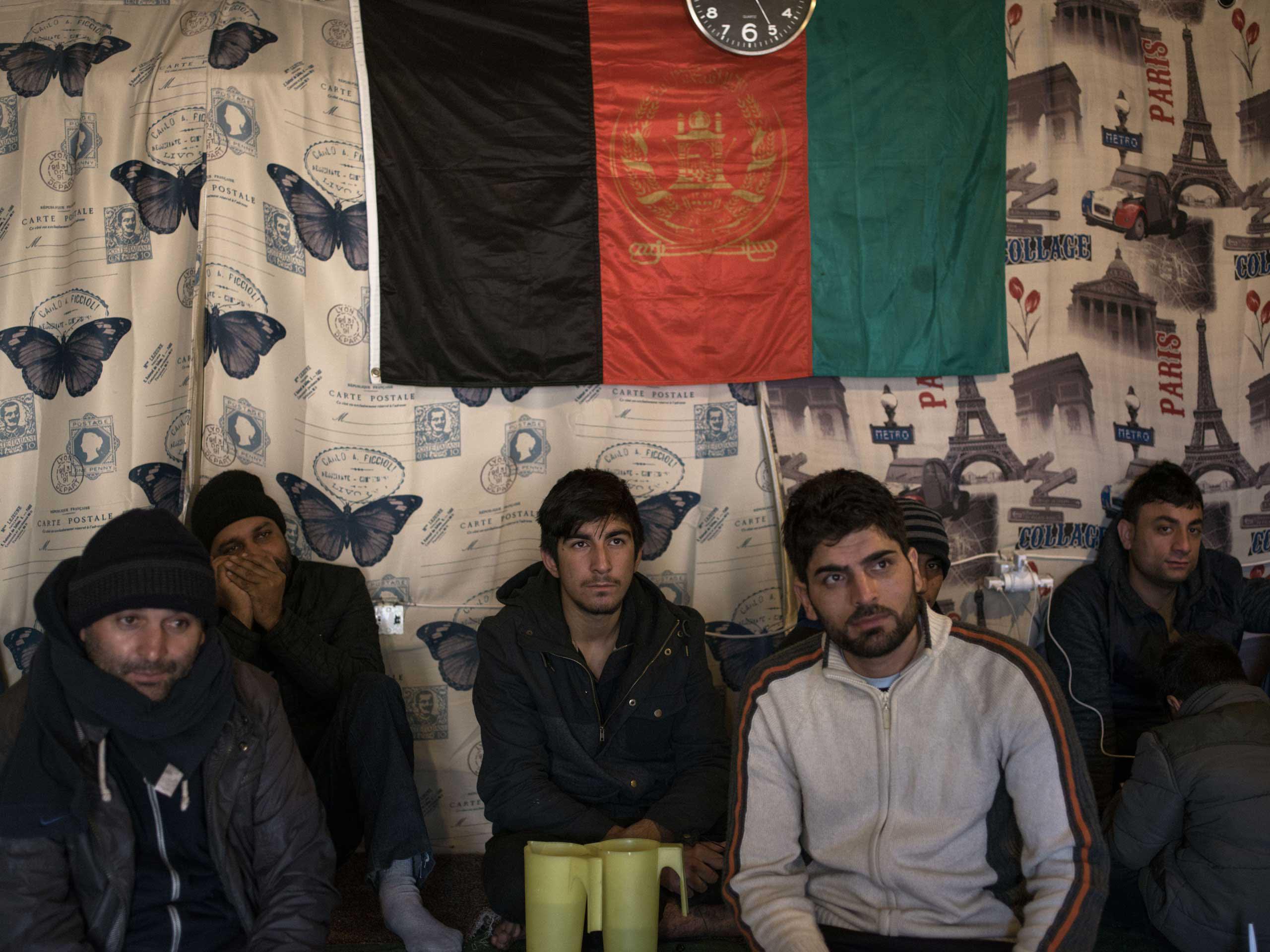 Men sit at an Afghan restaurant in the  jungle , Calais, France, Nov. 25, 2015.