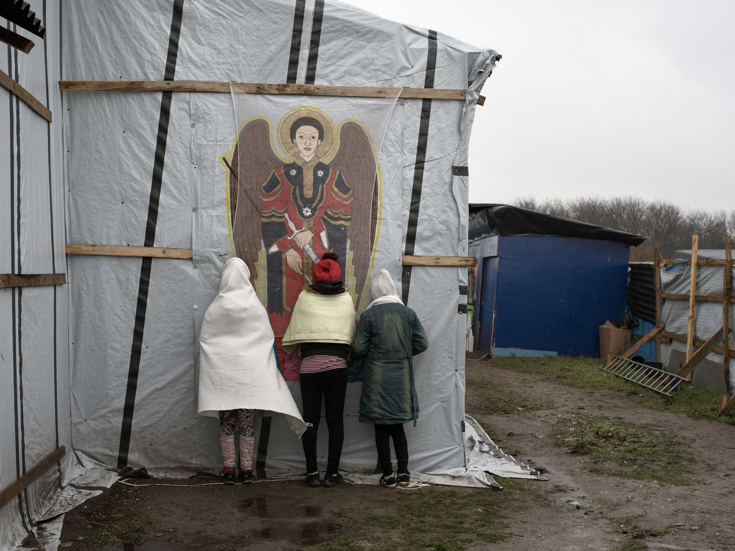 Orthodox Christians pray outside the makeshift church known as St. Michael's Calais  for the Ethiopian and Eritrean community in the  jungle  of Calais, France, Nov. 24, 2015.
