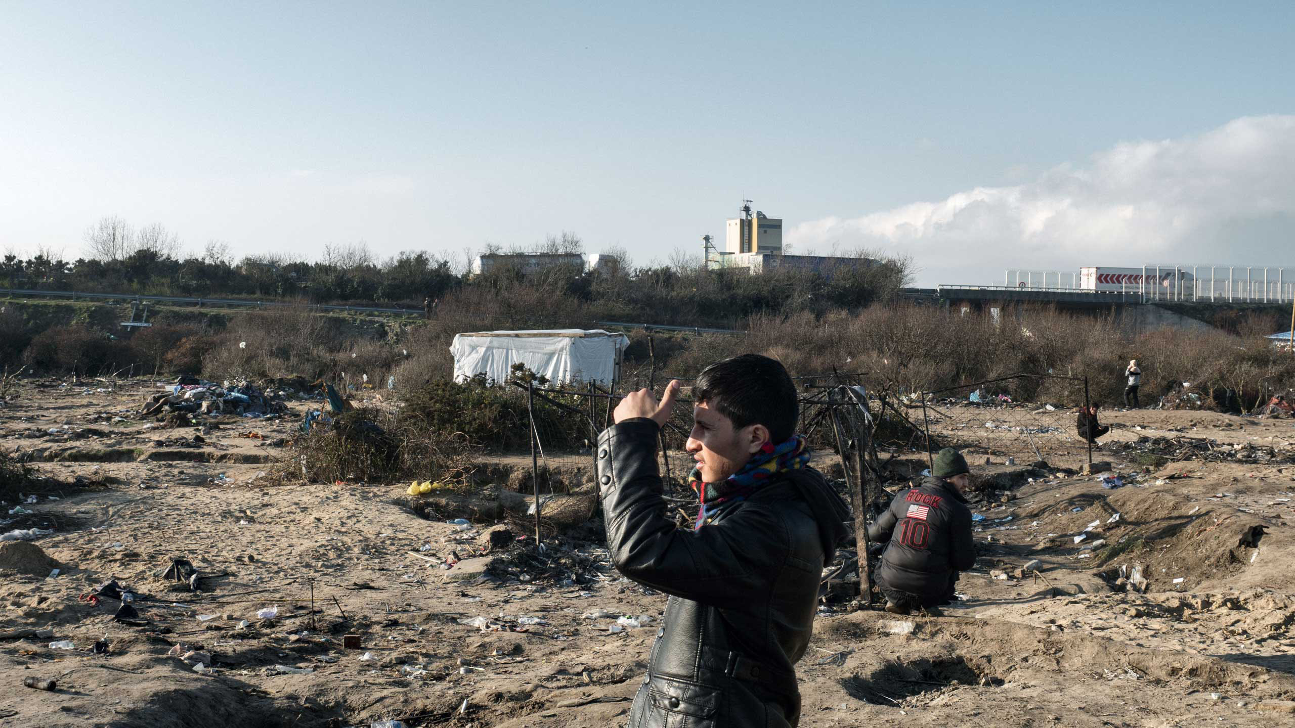 A young man looks out in an area in Calais, France that is being cleared for new housing containers, Jan. 20, 2016.