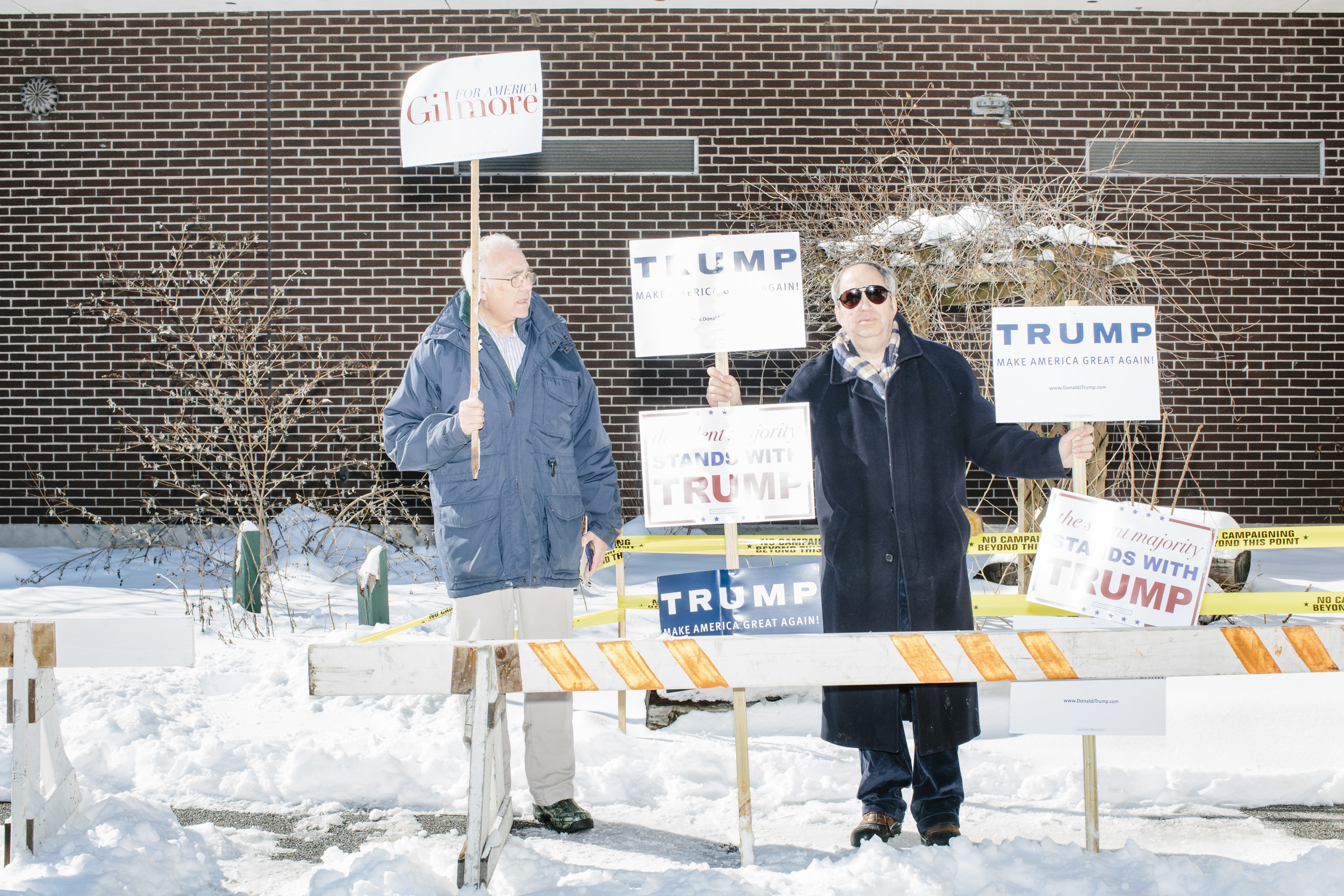 Lloyd Gatling, (left) of Suffolk, Virginia, brother-in-law of former Virginia governor and Republican presidential candidate Jim Gilmore holds campaign signs for the candidate outside the polling location for Manchester Ward 2 at Hillside Middle School in Manchester, New Hampshire, on the day of primary voting, Feb. 9, 2016. Also pictured is Jack Cohen, of Manchester, New Hampshire, a volunteer with the Trump campaign.