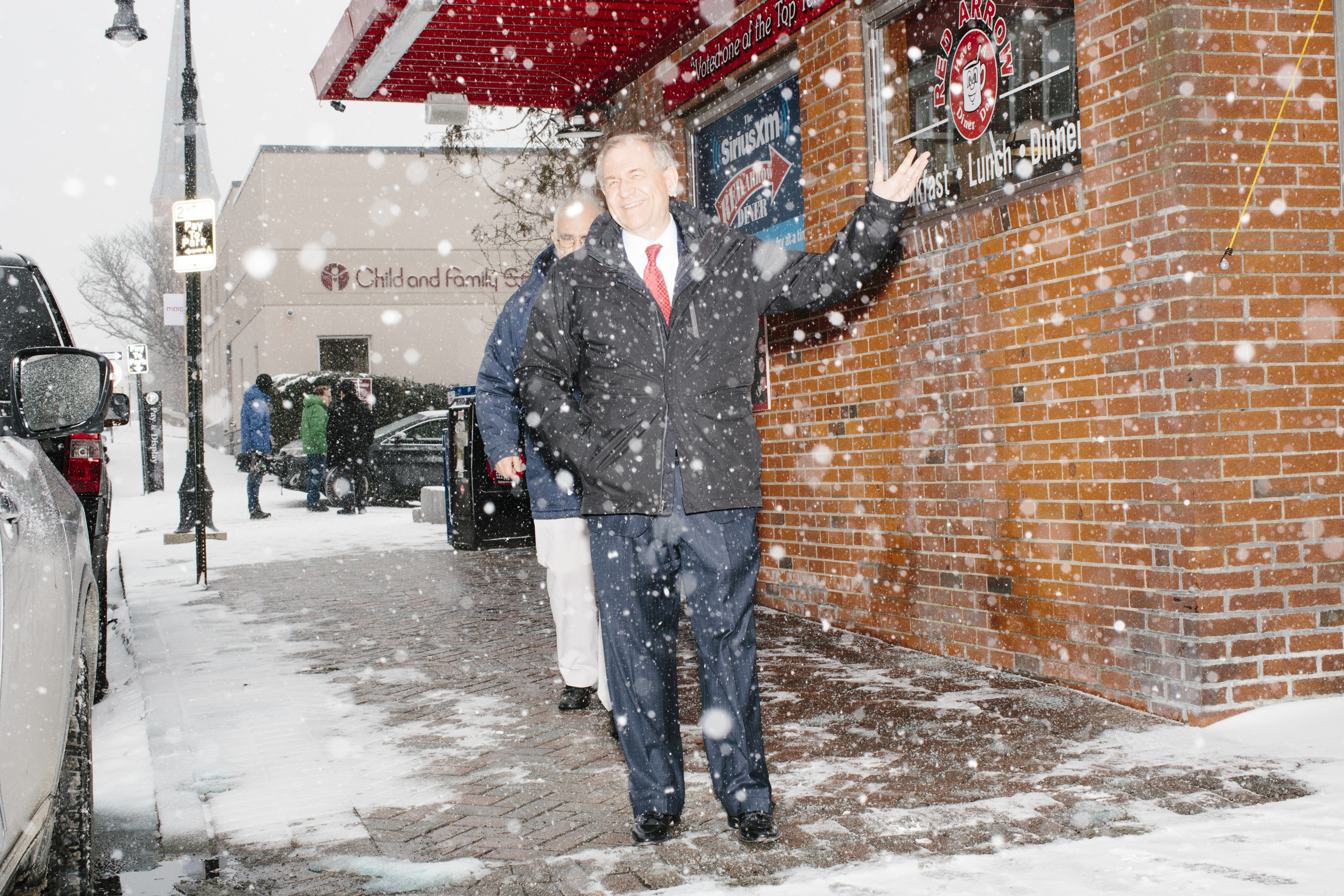 Former Virginia governor and Republican presidential candidate Jim Gilmore walks through the snow with brother-in-law Lloyd Gatling, of Suffolk, Virginia, after visit the Red Arrow Diner in Manchester, New Hampshire, on Mon., Feb. 8, 2016. The Red Arrow Diner is a frequent stop of political candidates. Sirius XM was broadcasting live from the diner Monday and Tuesday.