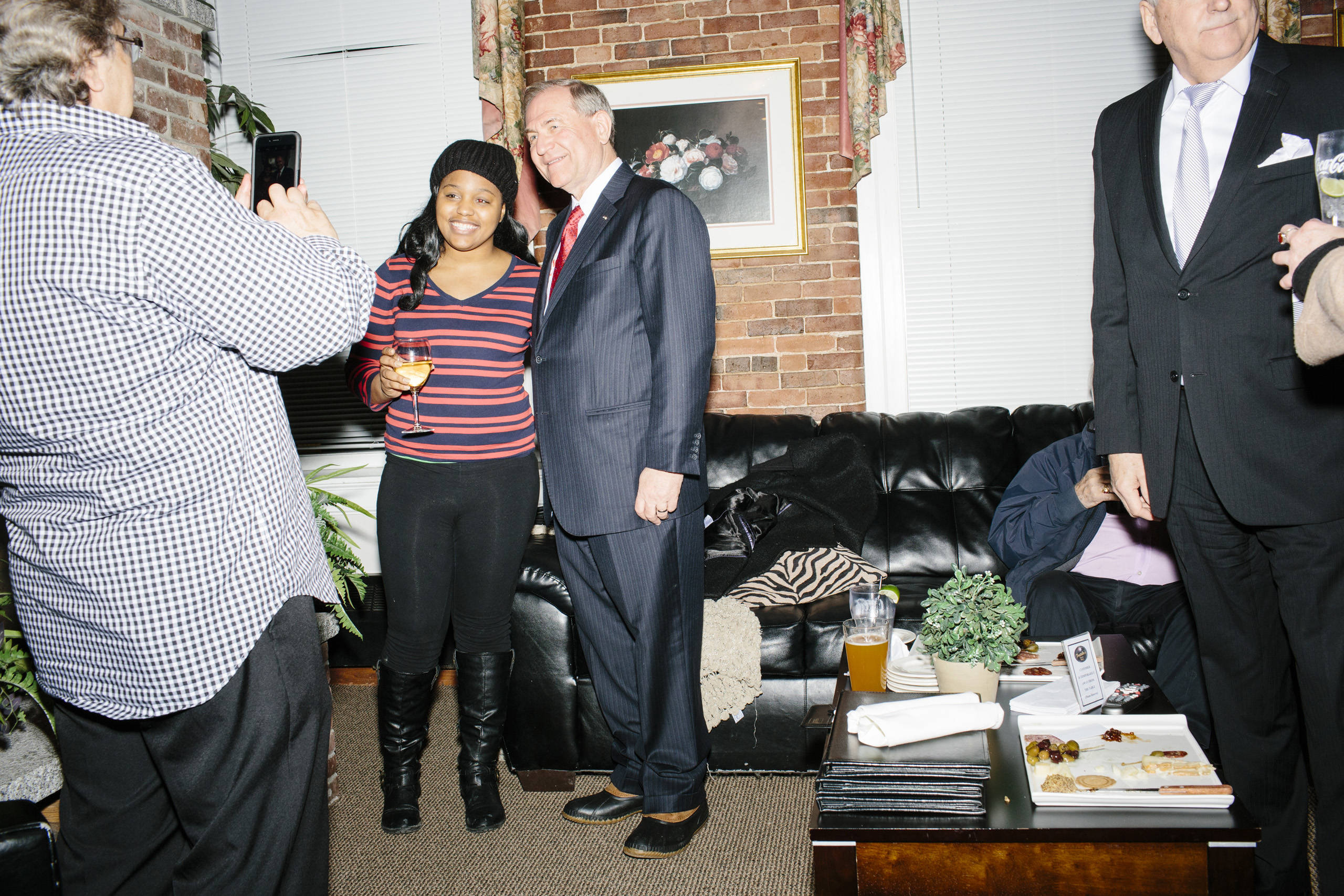 Former Virginia governor and Republican presidential candidate Jim Gilmore speaks with Gary LaBella, of Arlington, Virginia, (checkered shirt) and Lauren Green, of Silver Spring, Maryland, a Master's student in Political Communications at American University, at the Gilmore primary watch party at Fratello's in Manchester, New Hampshire on the day of primary voting, Feb. 9, 2016. LaBella came to the party because he said Gilmore was a good governor in Virginia. He was in the state for the primary acting as a chaperone for American University students visiting to watch the process.