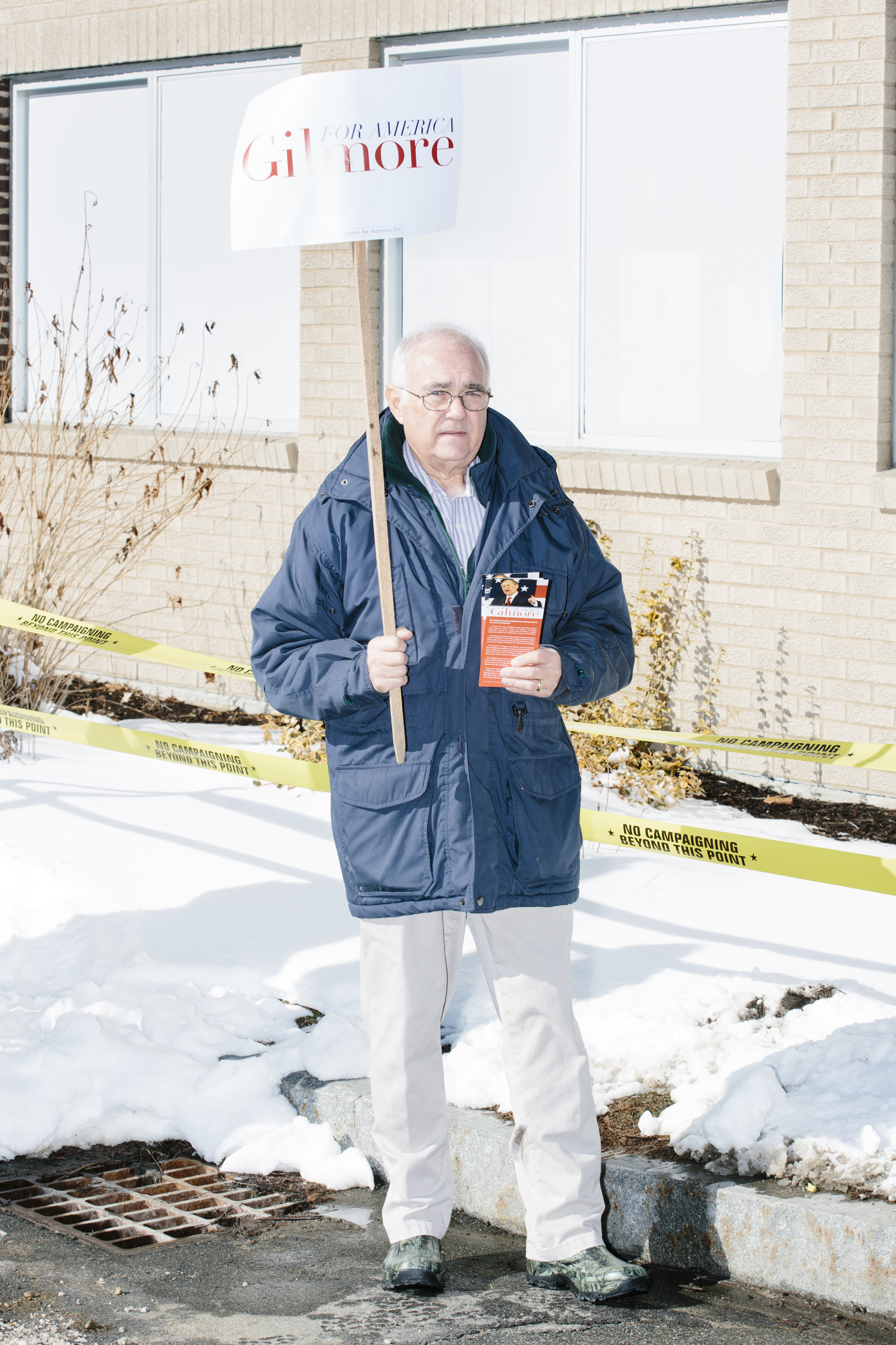 Lloyd Gatling, of Suffolk, Virginia, brother-in-law of former Virginia governor and Republican presidential candidate Jim Gilmore holds campaign signs for the candidate outside the polling location for Manchester Ward 2 at Hillside Middle School in Manchester, New Hampshire, on the day of primary voting, Feb. 9, 2016.
